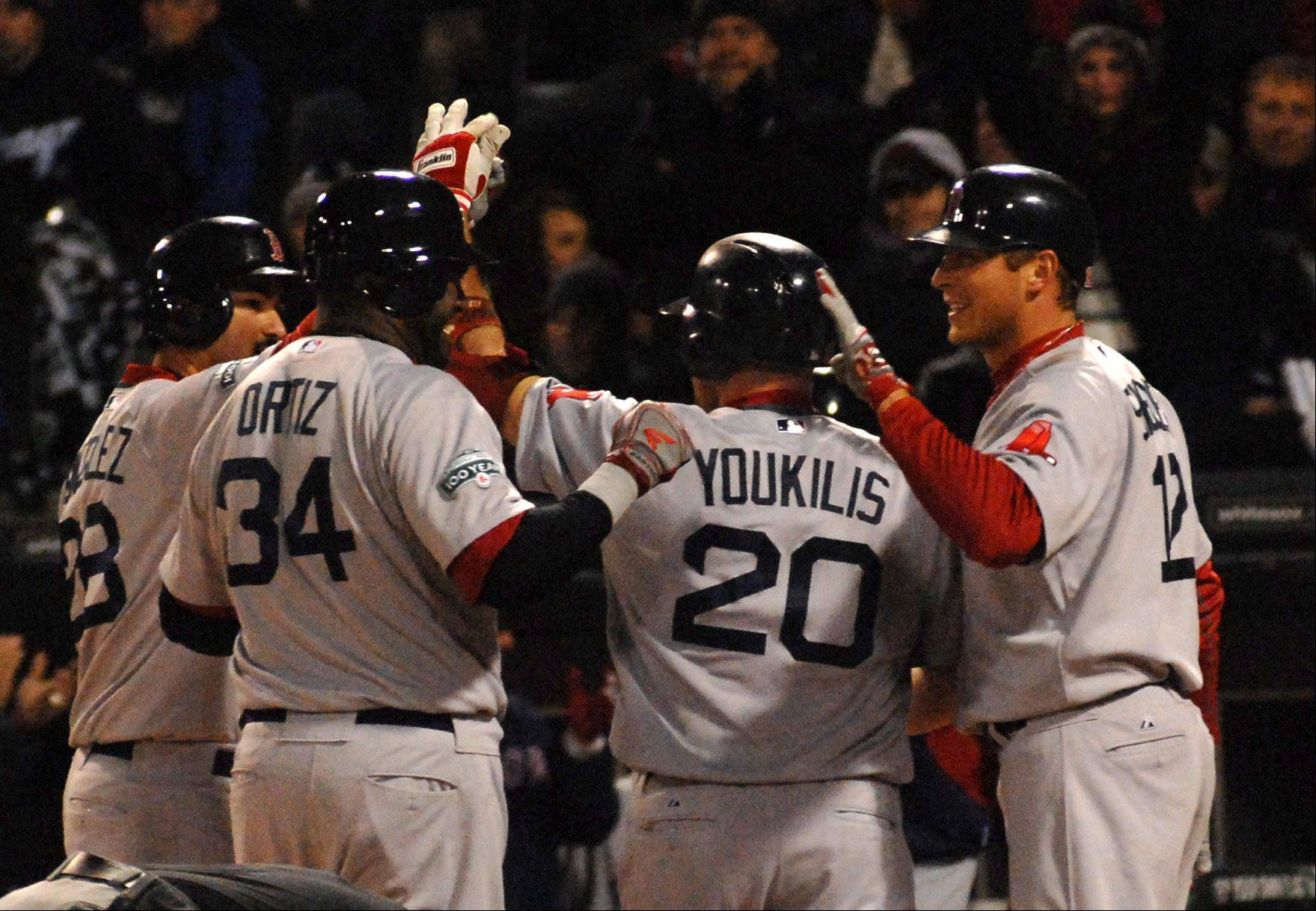 Red Sox teammates meet Kevin Youkilis at the plate after his third-inning grand slam.