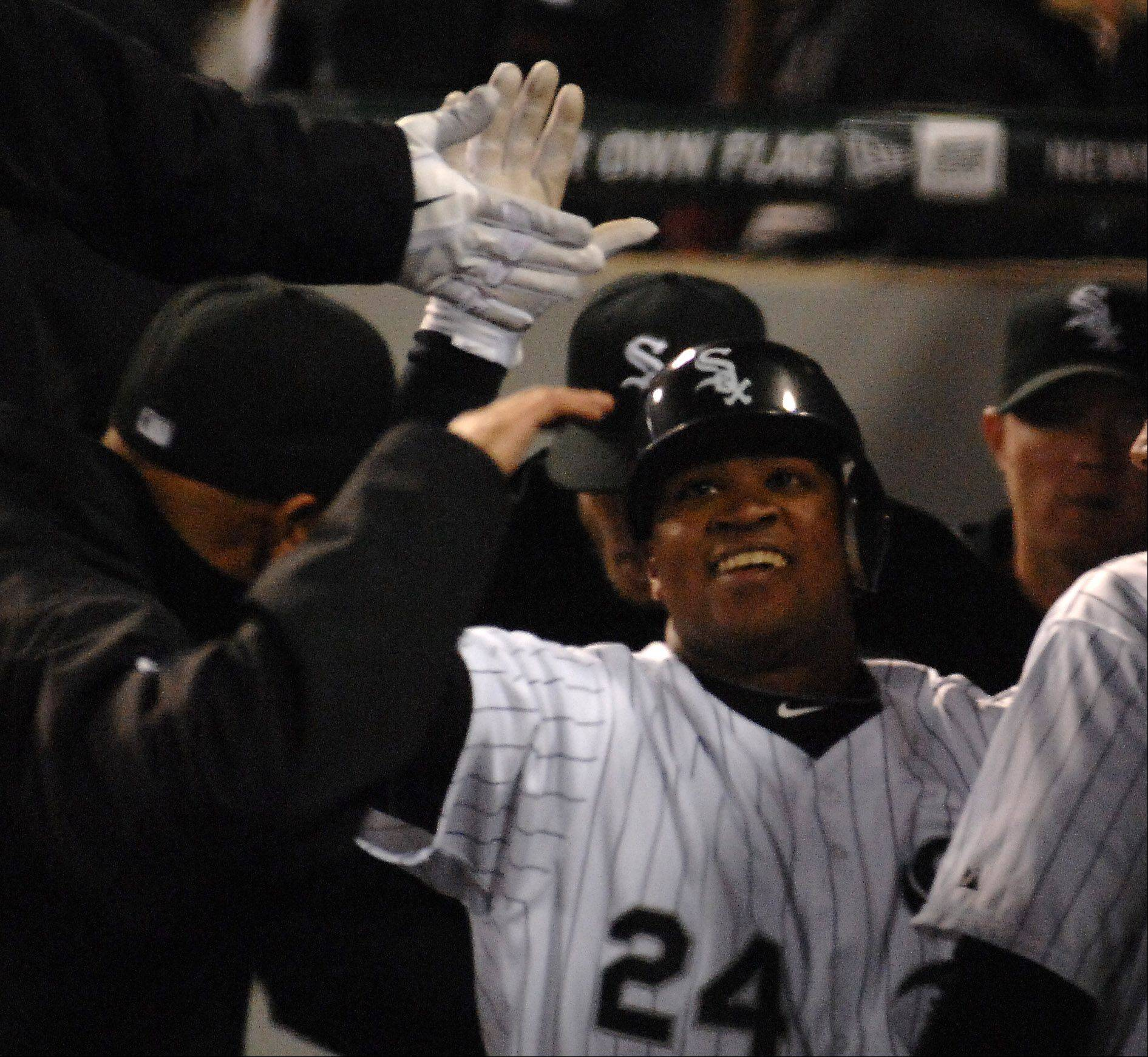 Dayan Viciedo is high-fived by White Sox teammates after his fourth-inning home run.