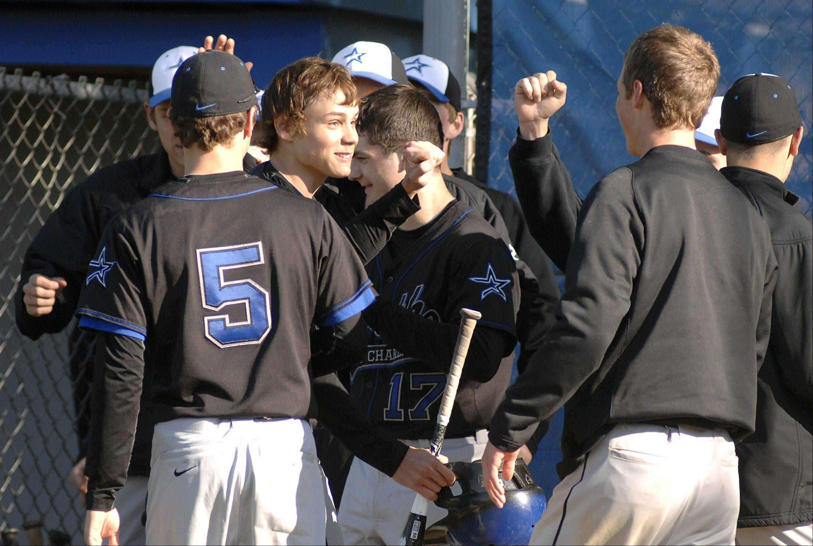 St. Charles North's Kevin Delisi, center, turns around to bumps fists with teammates after scoring a run in the fourth inning on Thursday, April 26.