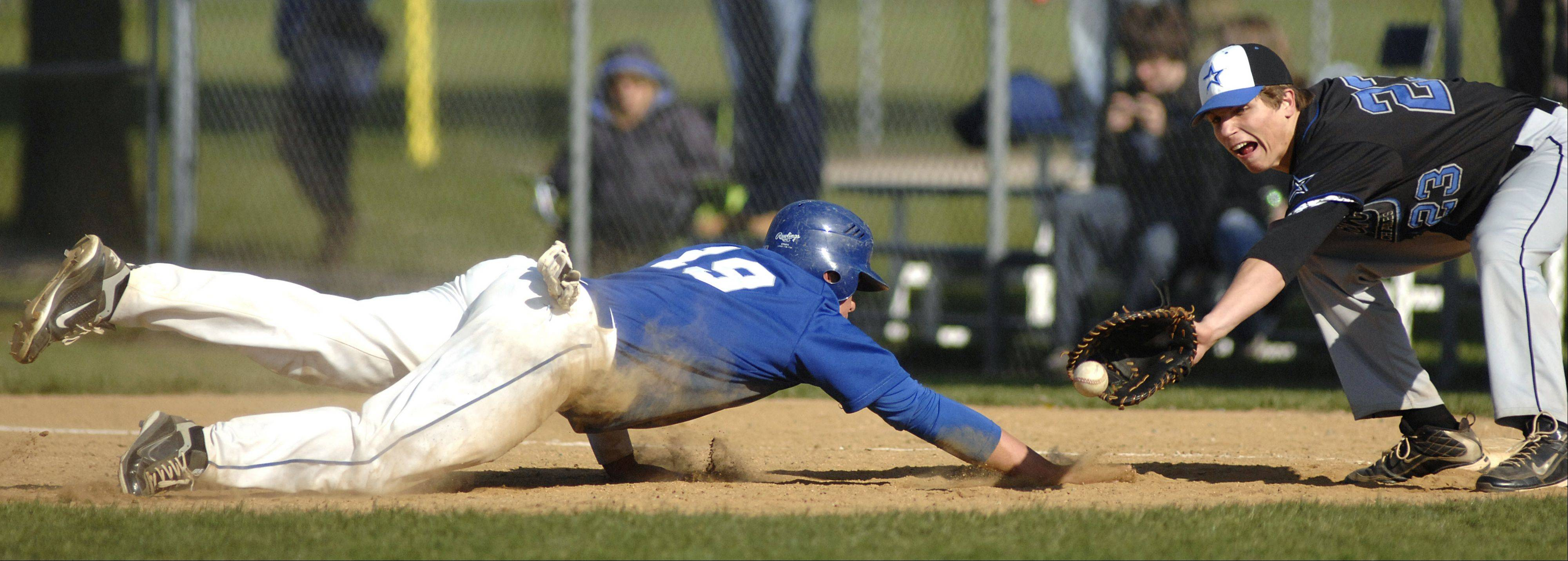 Laura Stoecker/lstoecker@dailyherald.comGeneva's Anthony Bragg is safe back on first base from St. Charles North's Ryan Thomas in the second inning on Thursday, April 26.
