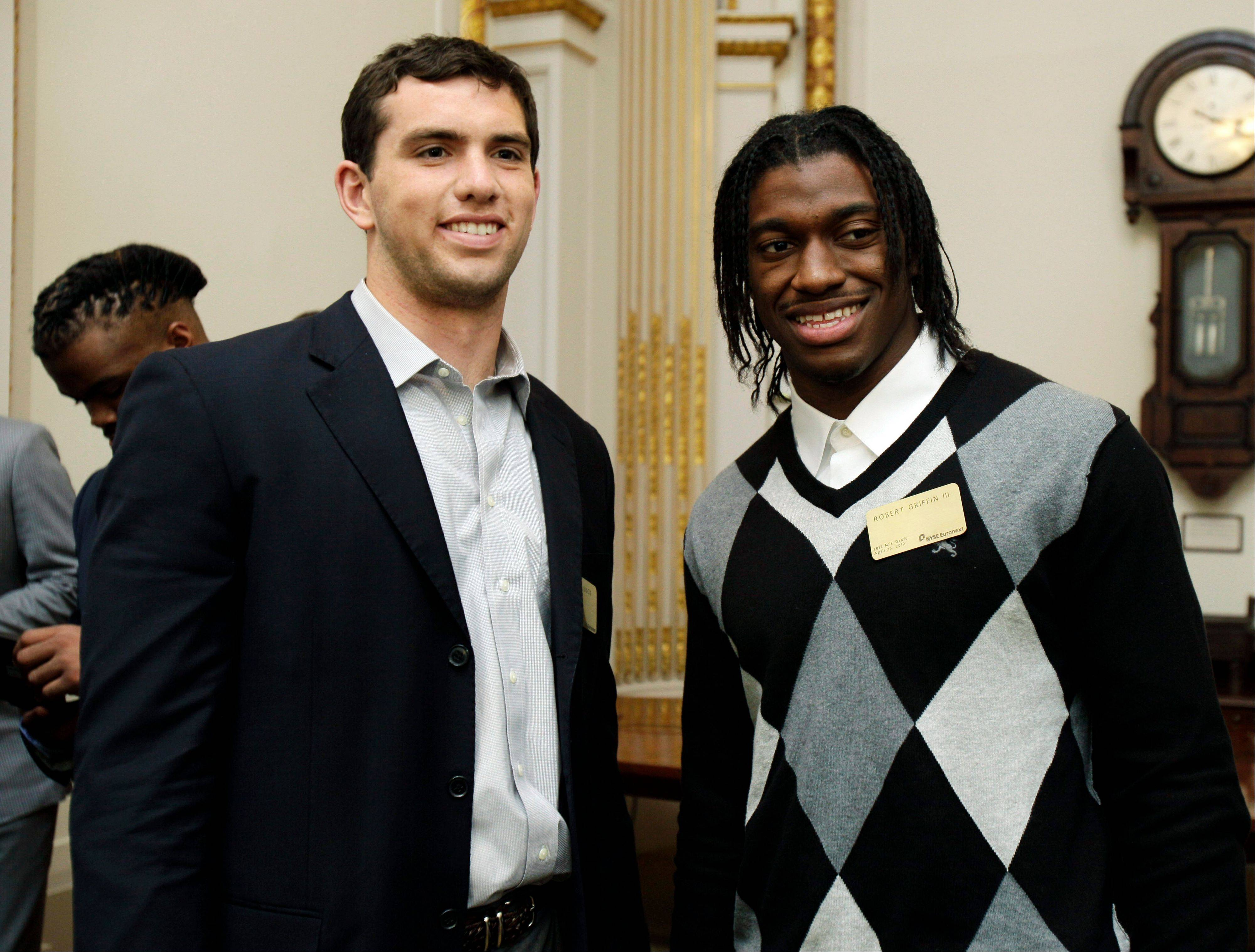 NFL football draft prospects Andrew Luck, left, of Stanford, and Robert Griffin III, of Baylor, attend a reception Wednesday during their visit to the trading floor of the New York Stock Exchange. With no doubt who the top two picks are, Minnesota is unofficially on the clock.
