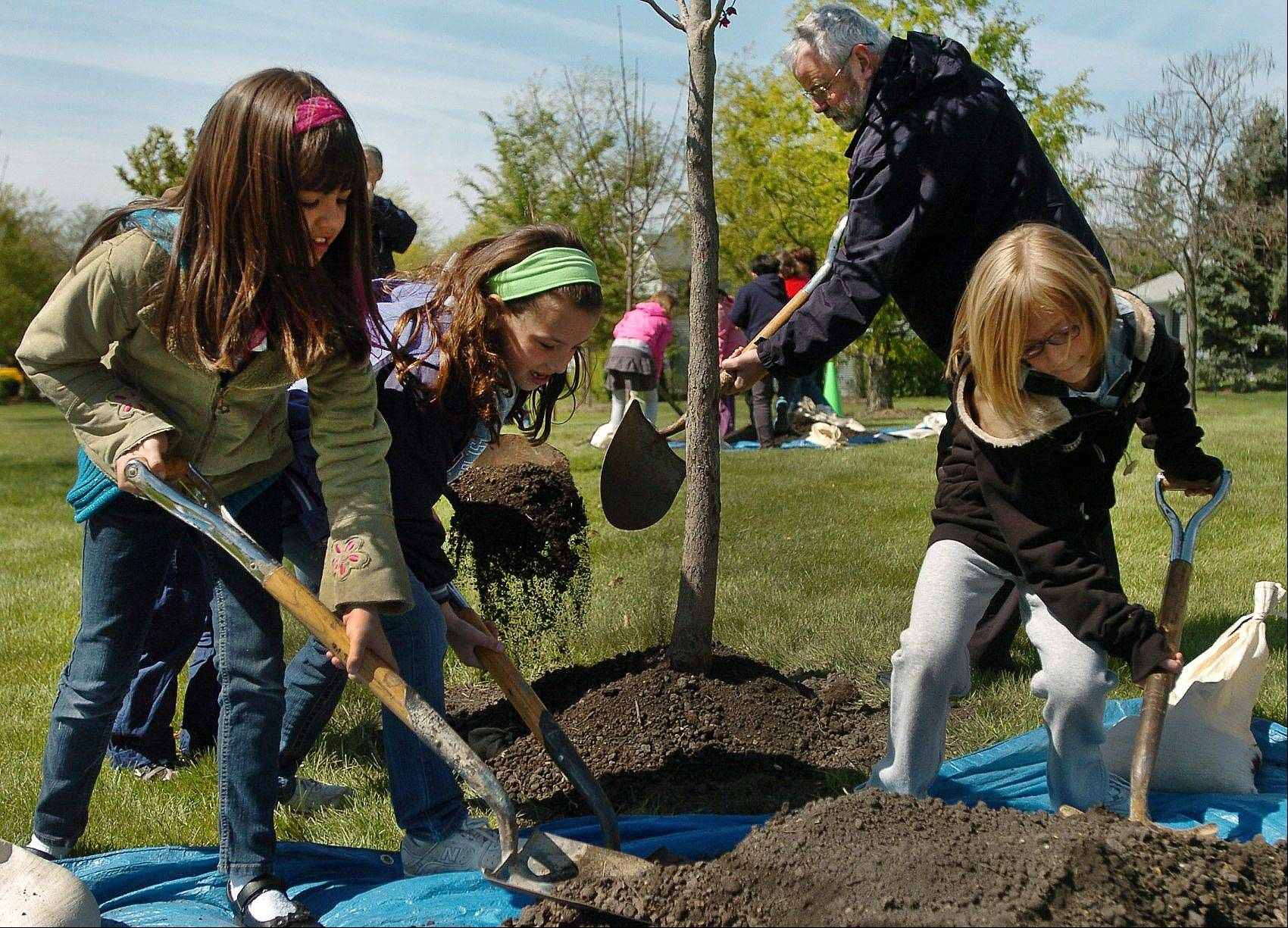 Frank C. Whiteley School third-graders, from left, Michaela Vall, Ashley Scesniak and Kailey Mleko help Mayor Bill McLeod at Arbor Day Park in Hoffman Estates.
