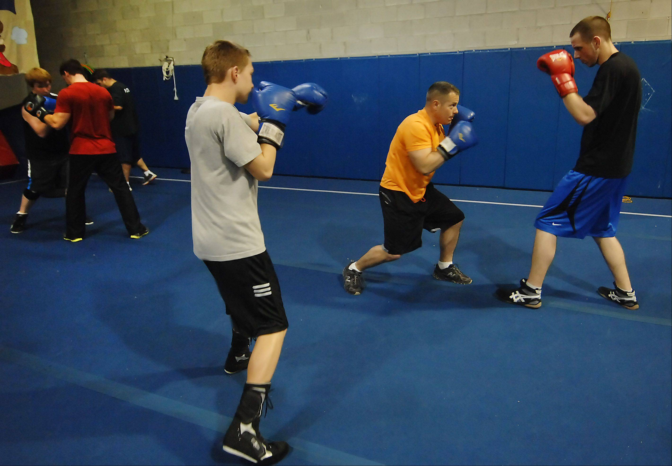 Paul Jonas, in the orange shirt, is launching Poundit Boxing Promotions by having a boxing exhibition this weekend. He coaches several people in the sport each night in Cary, including Jimmy Gustafson, 16, left, of Lake in the Hills and Tanner Frese, 19, of Cary.