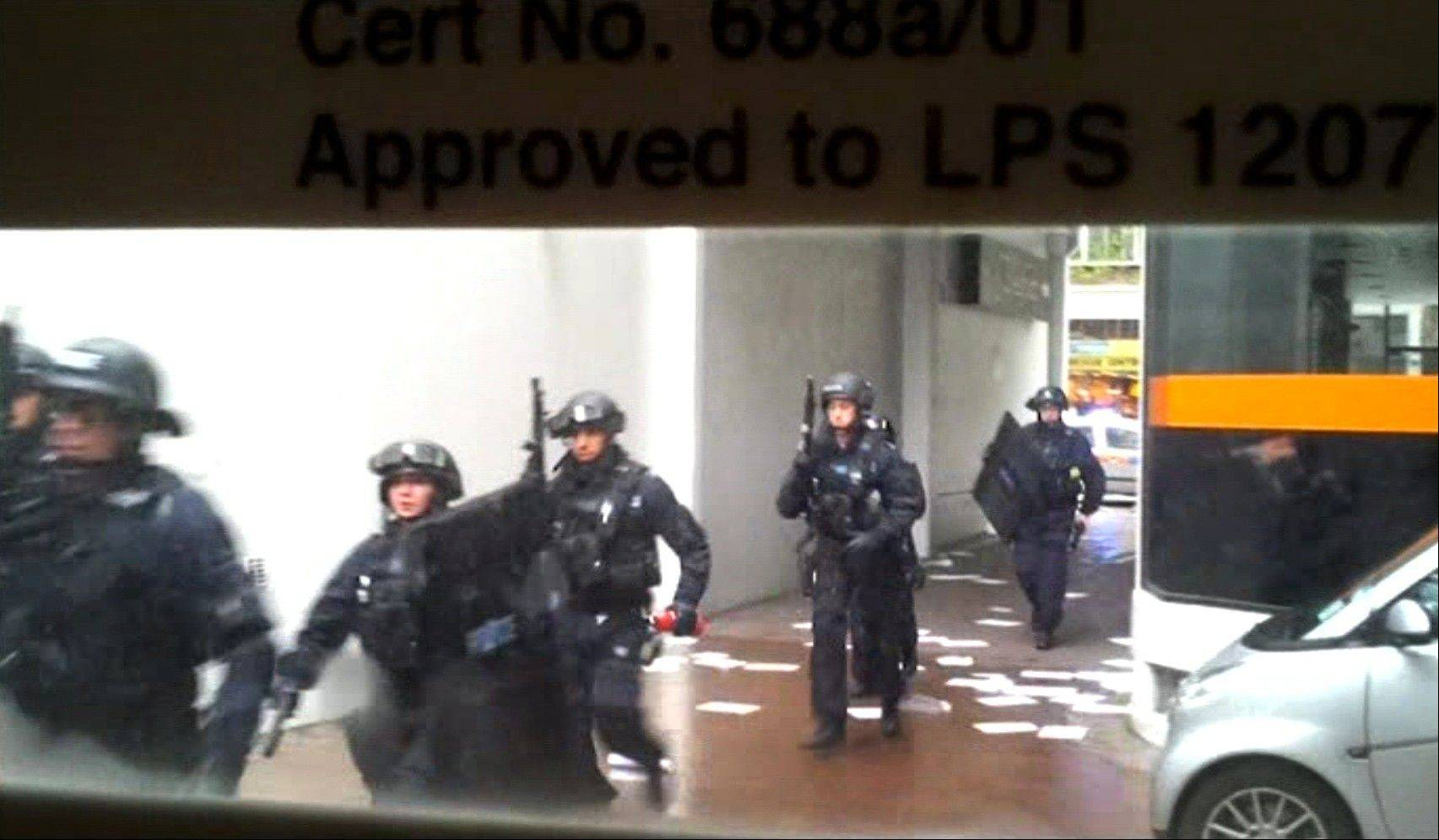 This video image taken from amateur video shows heavily armed, masked police entering a building in central London Friday.