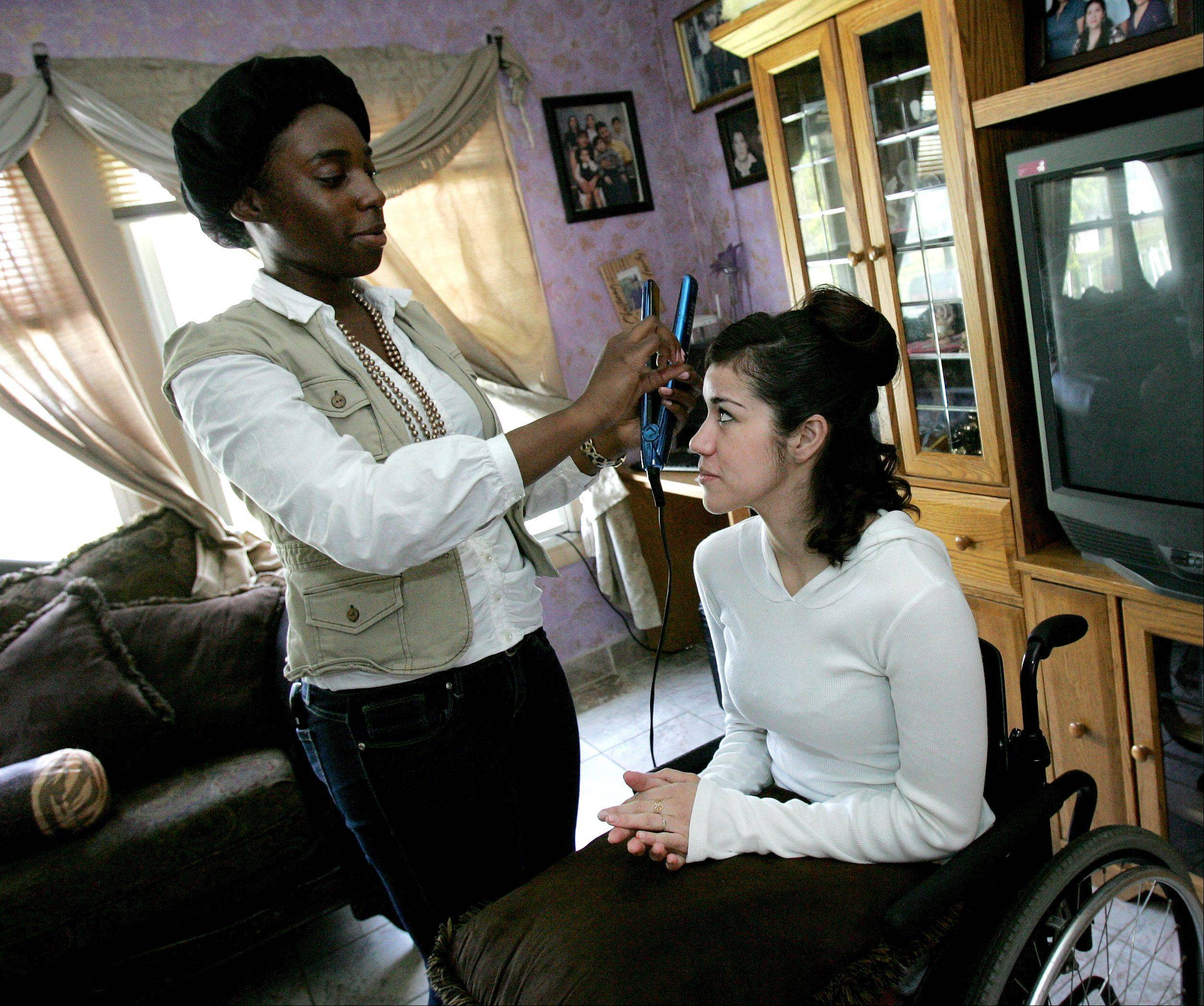 Leeslyee Huerta of Bolingbrook gets her hair done by Metea Valley High School senior Amber Moore as she prepares for senior prom on Friday.