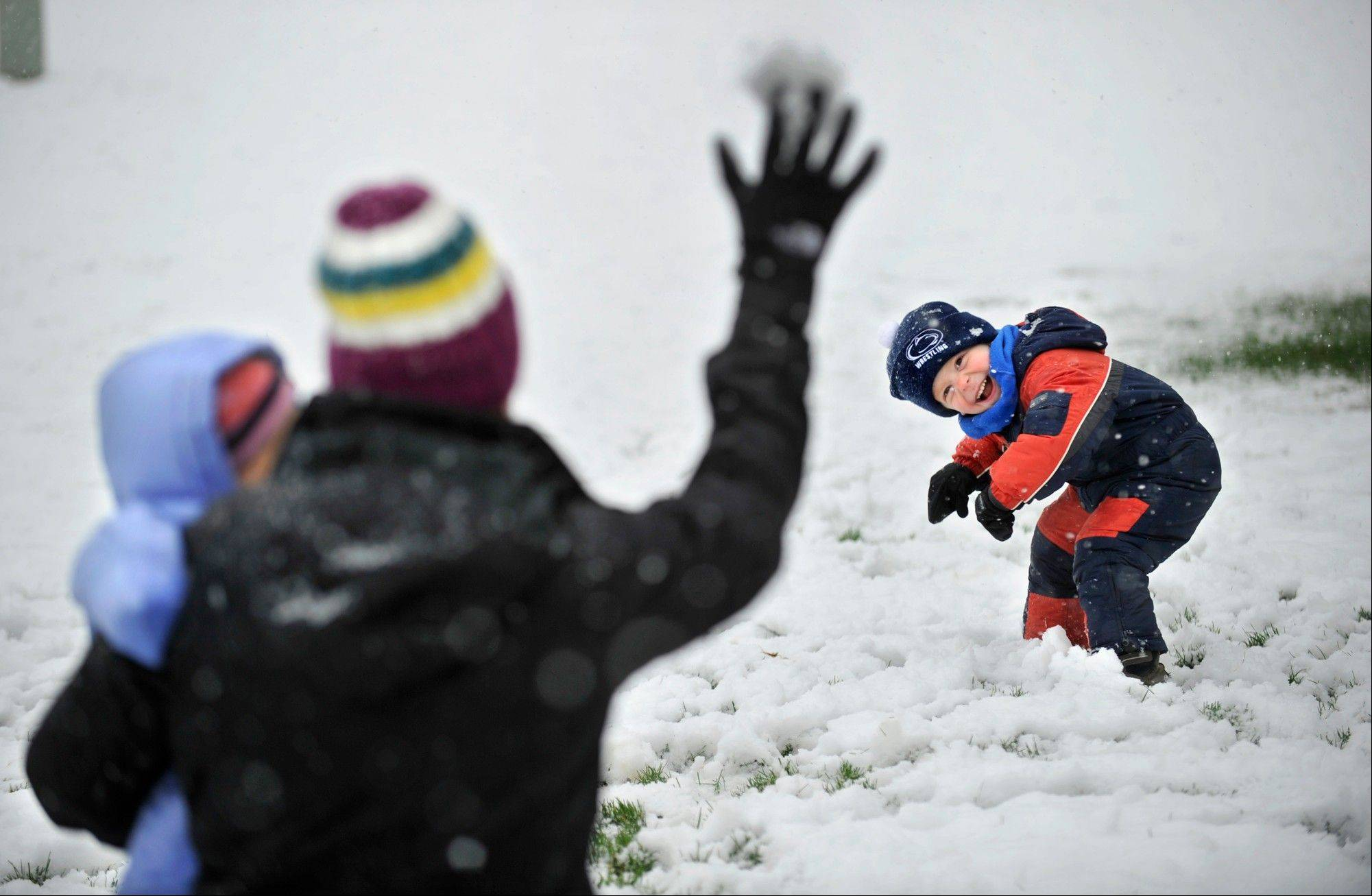 Evan Dreibelbis, 3, tries to avoid a snowball during a snowball fight in fresh snow in their front yard with his mother Dana Dreibelbis and sister Elle Monday, April 23, 2012 in Pine Grove Mills, Pa. A spring nor'easter packing soaking rain and high winds churned up the Northeast Monday morning, unleashing a burst of winter and up to a foot of snow in higher elevations inland, closing some schools and sparking concerns of power outages.