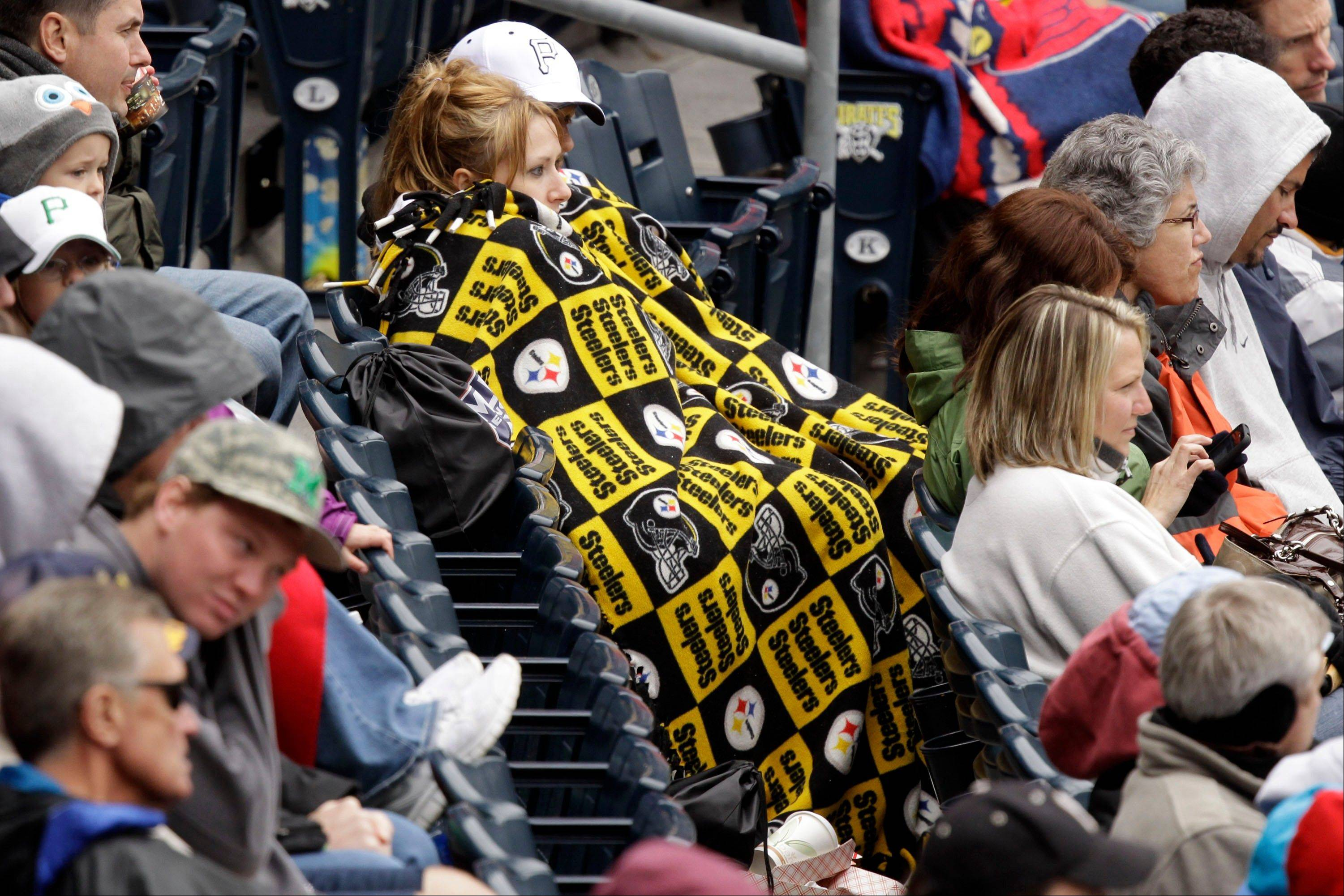Pittsburgh Pirates fans sit bundled in a Pittsburgh Steelers blanket while watching a baseball game between the St. Louis Cardinals and the Pirates in Pittsburgh on Sunday, April 22, 2012. The Cardinals won 5-1. A spring nor'easter rumbled along the East Coast on Sunday and was expected to bring rain and heavy winds and even snow in some places as it strengthens into early Monday, a punctuation to a relatively dry stretch of weather for the Northeast.