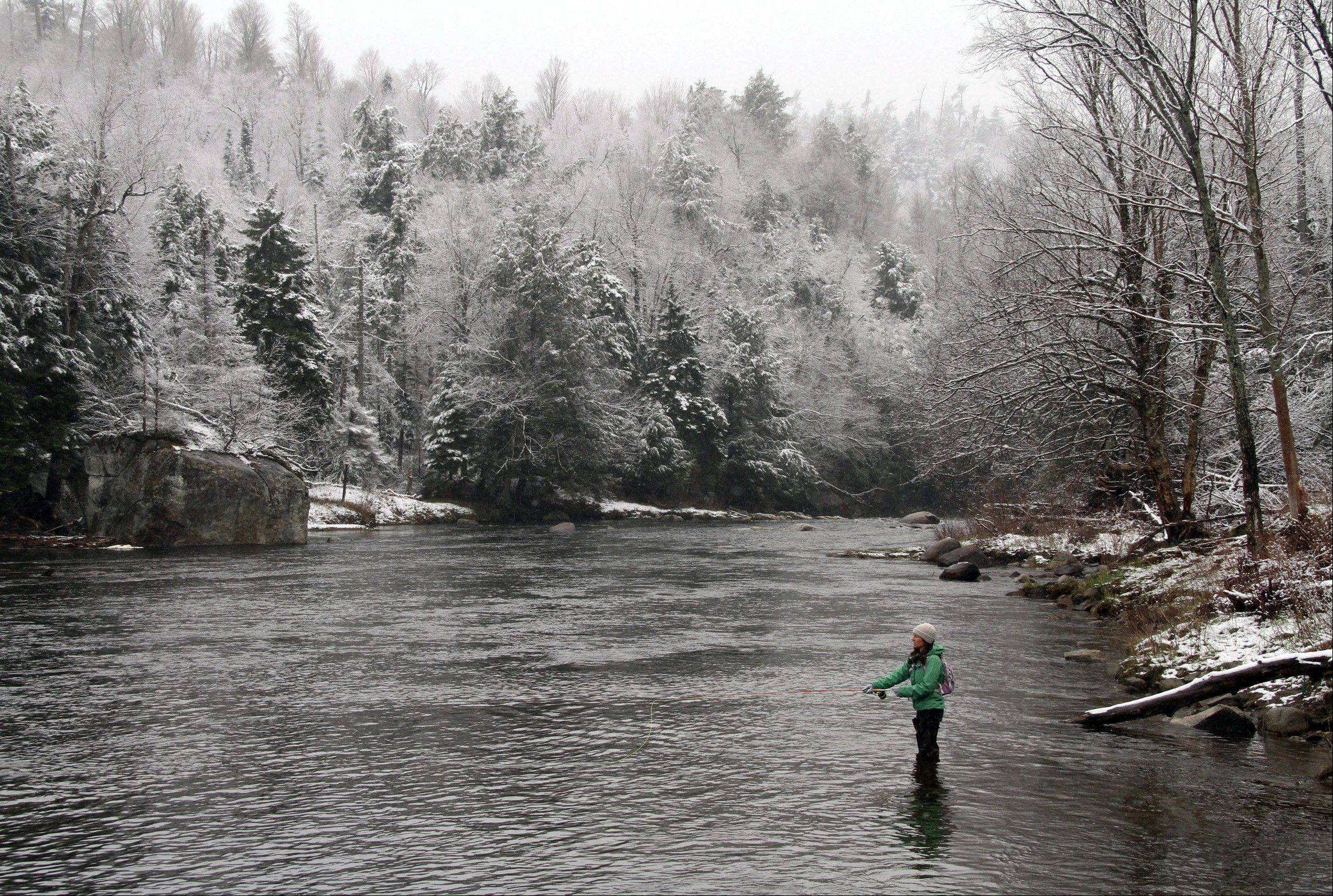 A woman fishes on the West Branch of the AuSable River in Wilmington, N.Y., after a snowfall on Sunday, April 22, 2012. A spring nor'easter along the East Coast on Sunday is expected to bring rain and heavy winds and even snow in some places as it strengthens into early Monday, a punctuation to a relatively dry stretch of weather for the Northeast.