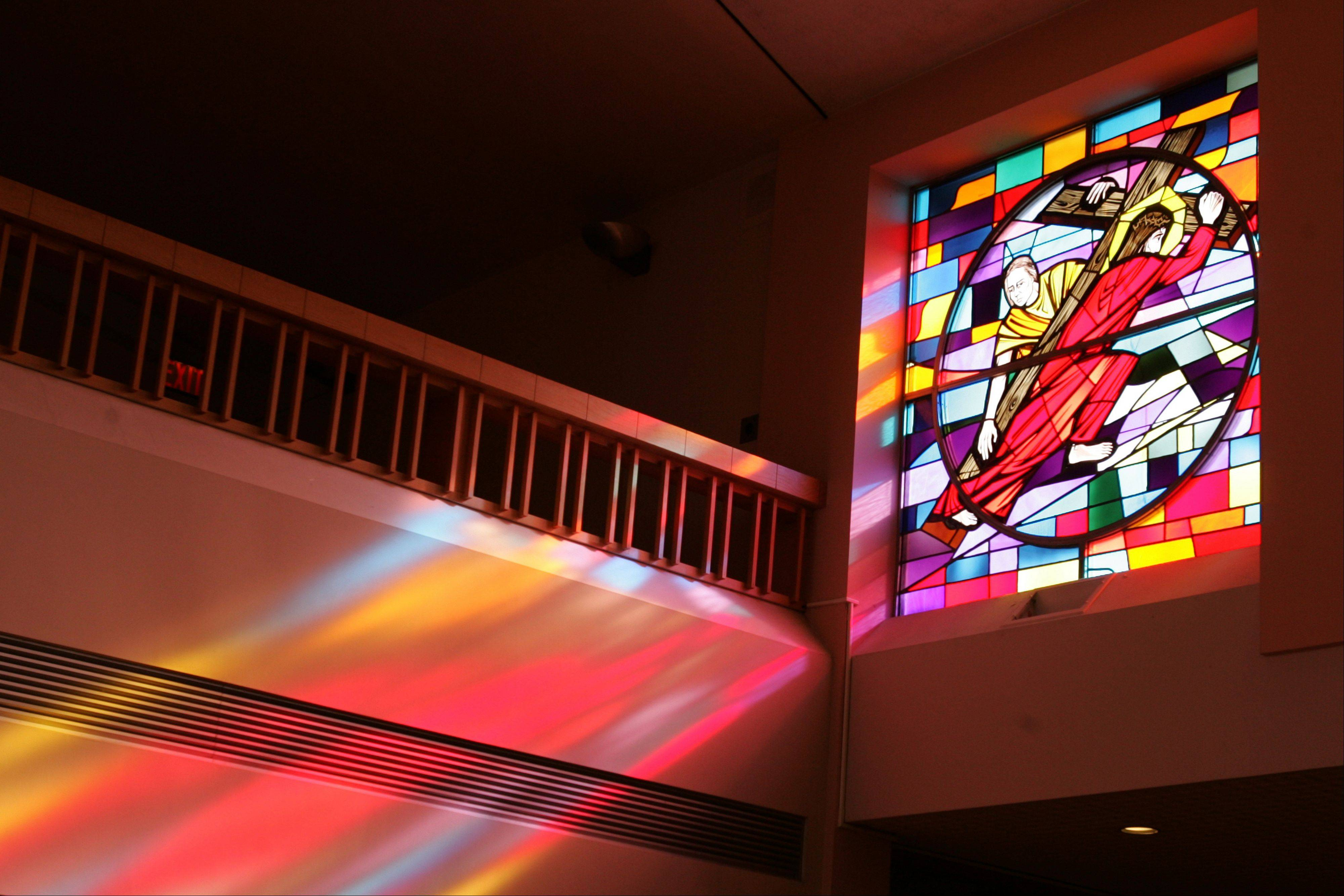 Light enters through a stained-glass window at St. Peter Catholic Church in Aurora.