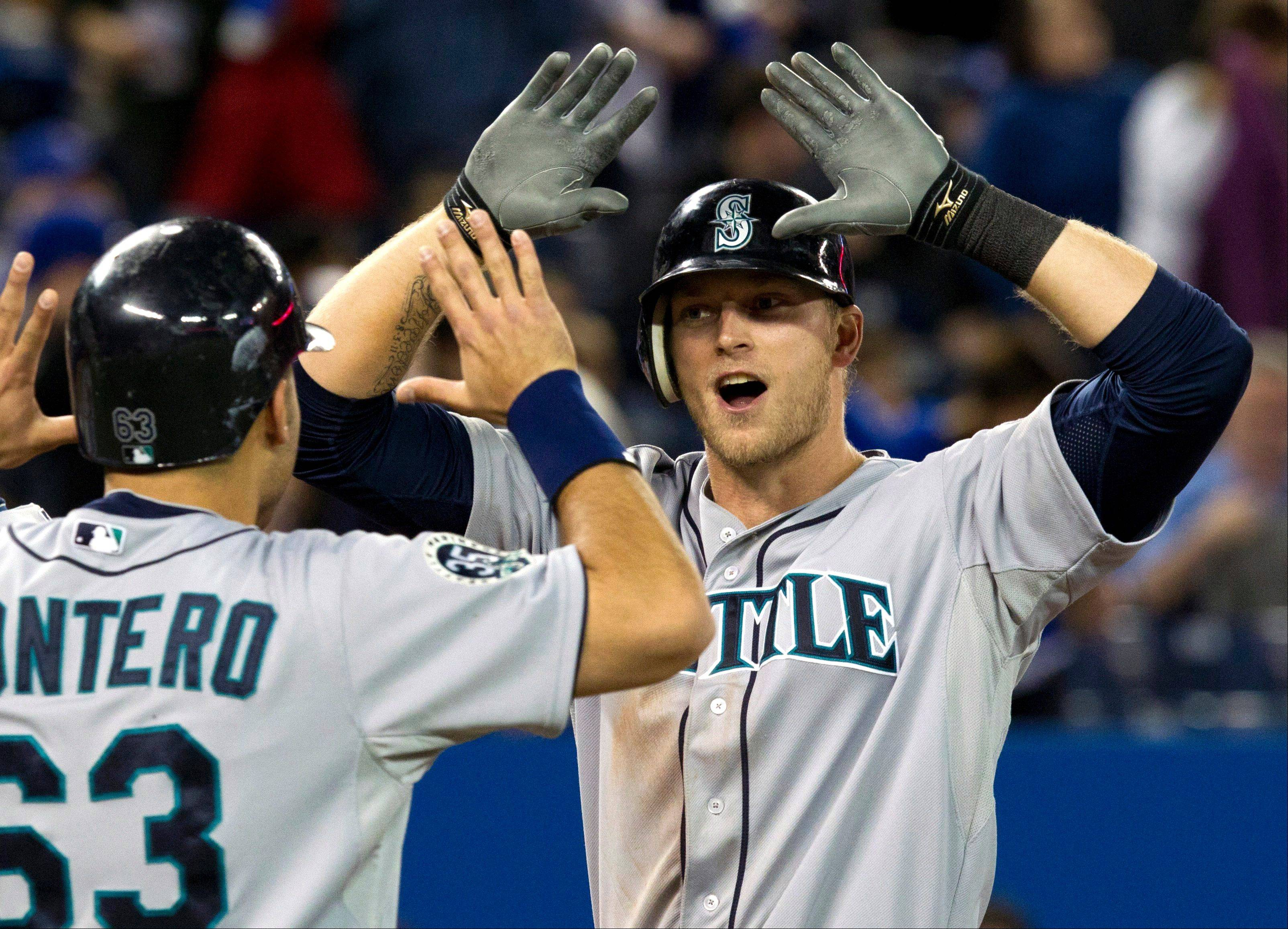 Seattle's Michael Saunders, right, celebrates his 10th-inning grand slam with teammate Jesus Montero on Friday in Toronto.