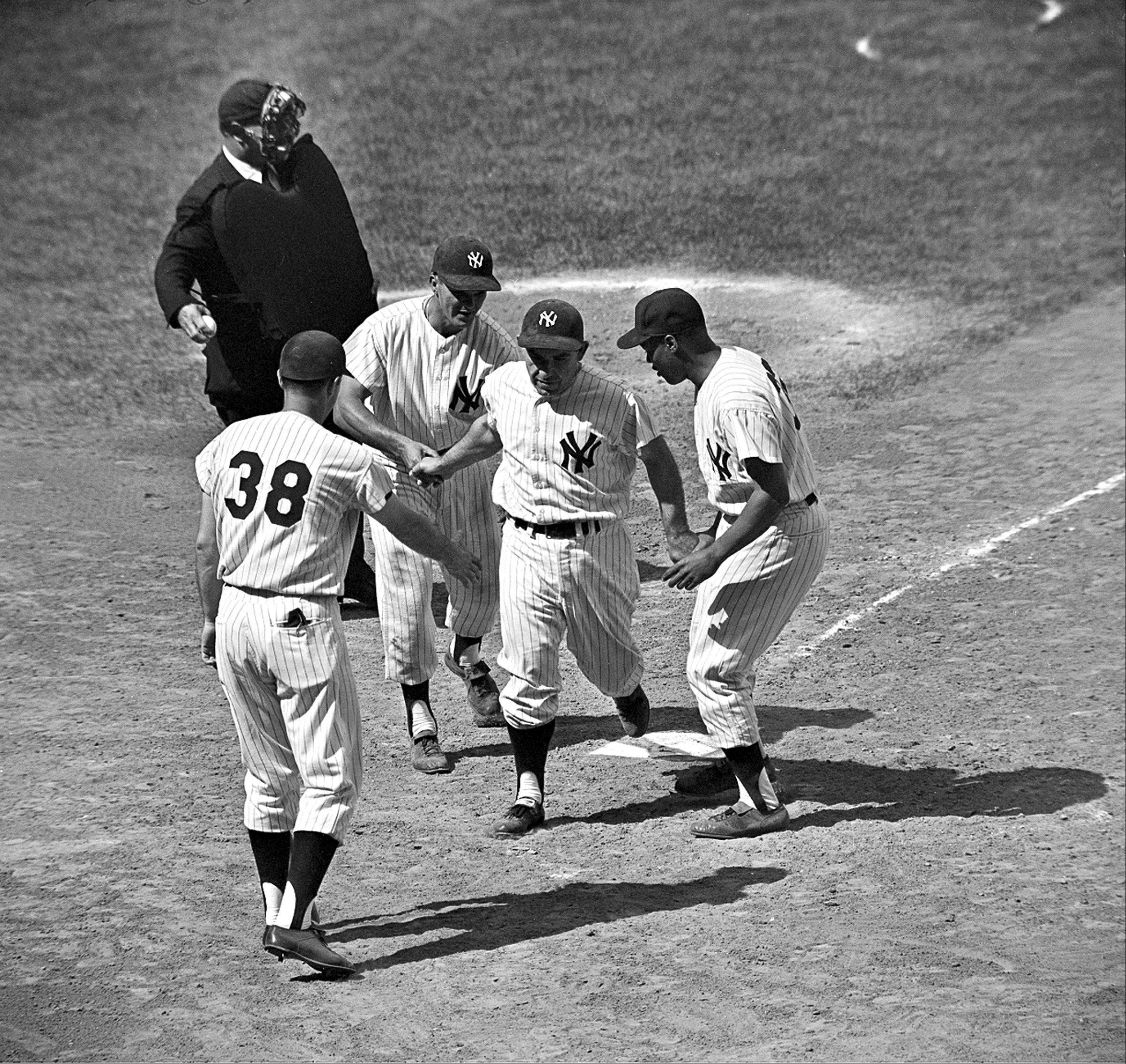 New York Yankees outfielder Yogi Berra receives congratulations from teammates after belting a three-run pinch hit homer in the seventh inning against the Baltimore Orioles at Yankee Stadium in the Bronx, N.Y., June 9, 1962. The game marks Berra's appearance in his 2,000th major league ball game. From left are, John Blanchard, next batter; Bill Skowron; Berra; and Elston Howard, who scored ahead of Berra. The Yankees won, 7-3.