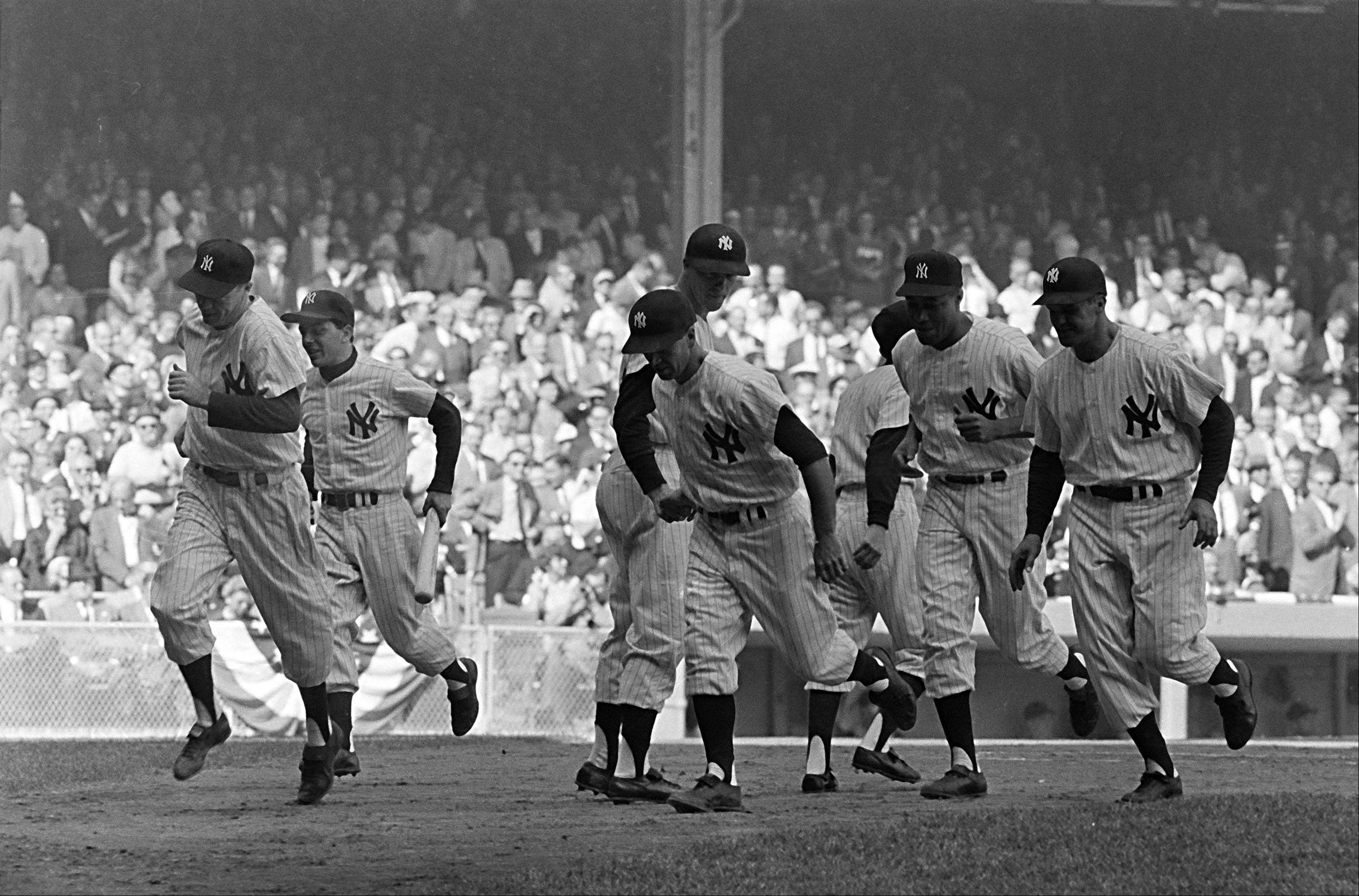 The Yankees were storming against the Pirates on Bobby Richardson's grand slam home run in first inning of third World Series game at Yankee Stadium, Oct. 8, 1960. And here they storm into dugout after the blast. Richardson is in center, head down, shaking hands with the next batter Tony Kubek. From left: Gil McDougald, batboy, Richardson, Elston Howard and Bill Skowron.