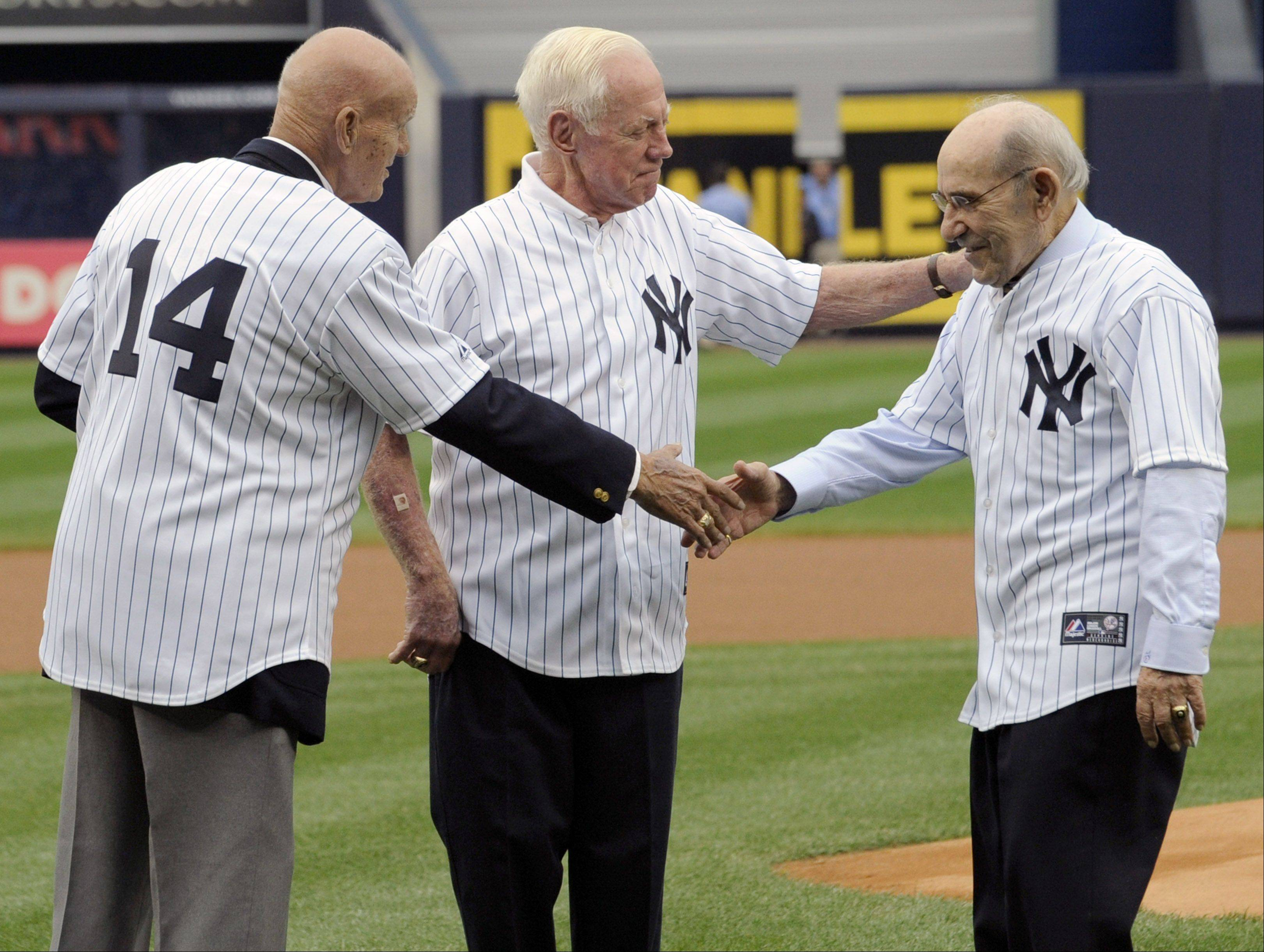 New York Yankees' Moose Skowron, left, and Whitey Ford welcome Yogi Berra, right, as they gather before the Yankees' baseball game against the Boston Red Sox on Saturday, Sept. 24, 2011, at Yankee Stadium in New York. The Yankees marked the 50th anniversary of Roger Maris' 61 home runs in 1961.