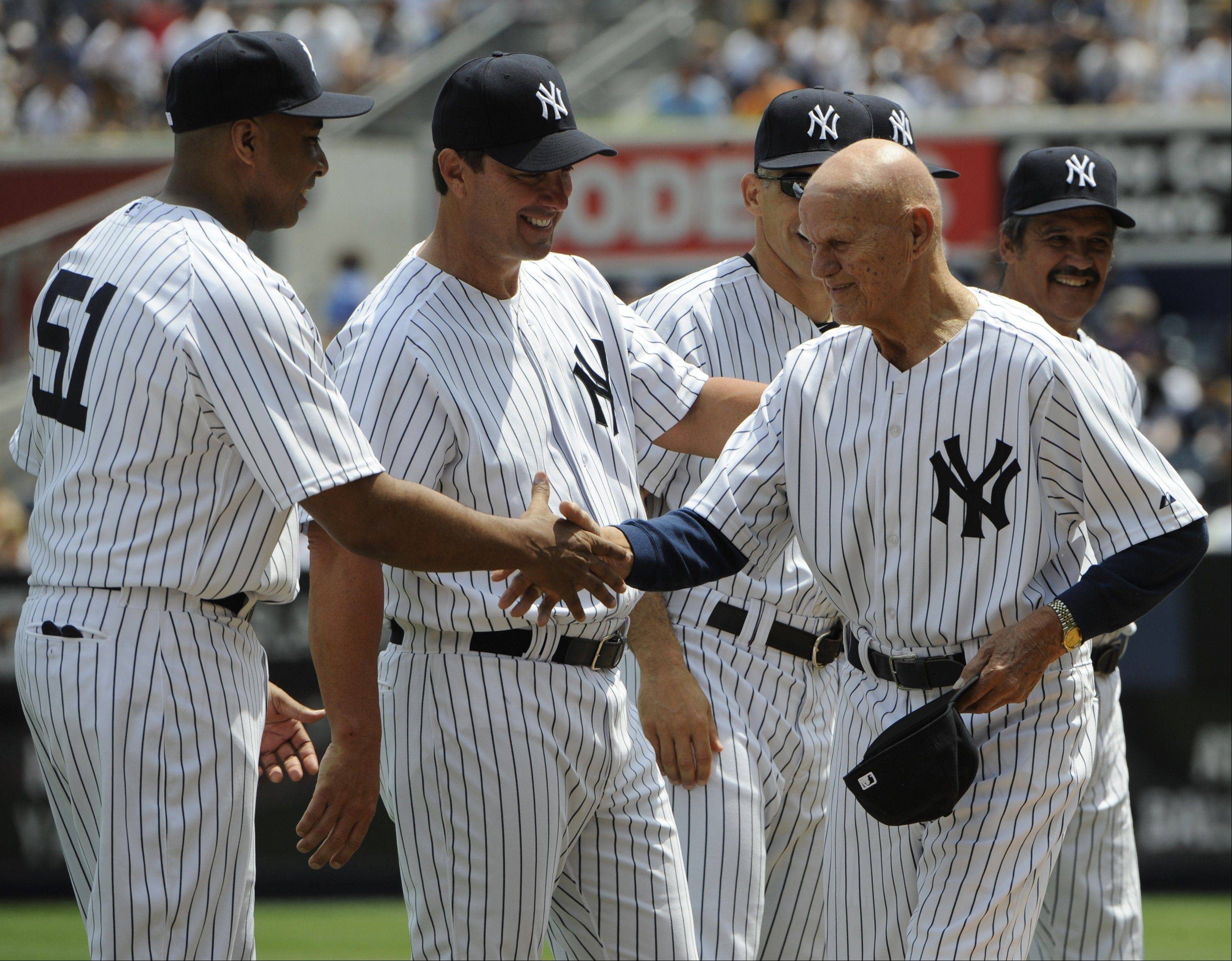 "Former New York Yankees first baseman BIll ""Moose"" Skowron, right, shakes hands with Bernie Williams, left, as Tino Martinez looks on during Old Timers' Day ceremonies last June at at Yankee Stadium in New York. Skowron died Friday."