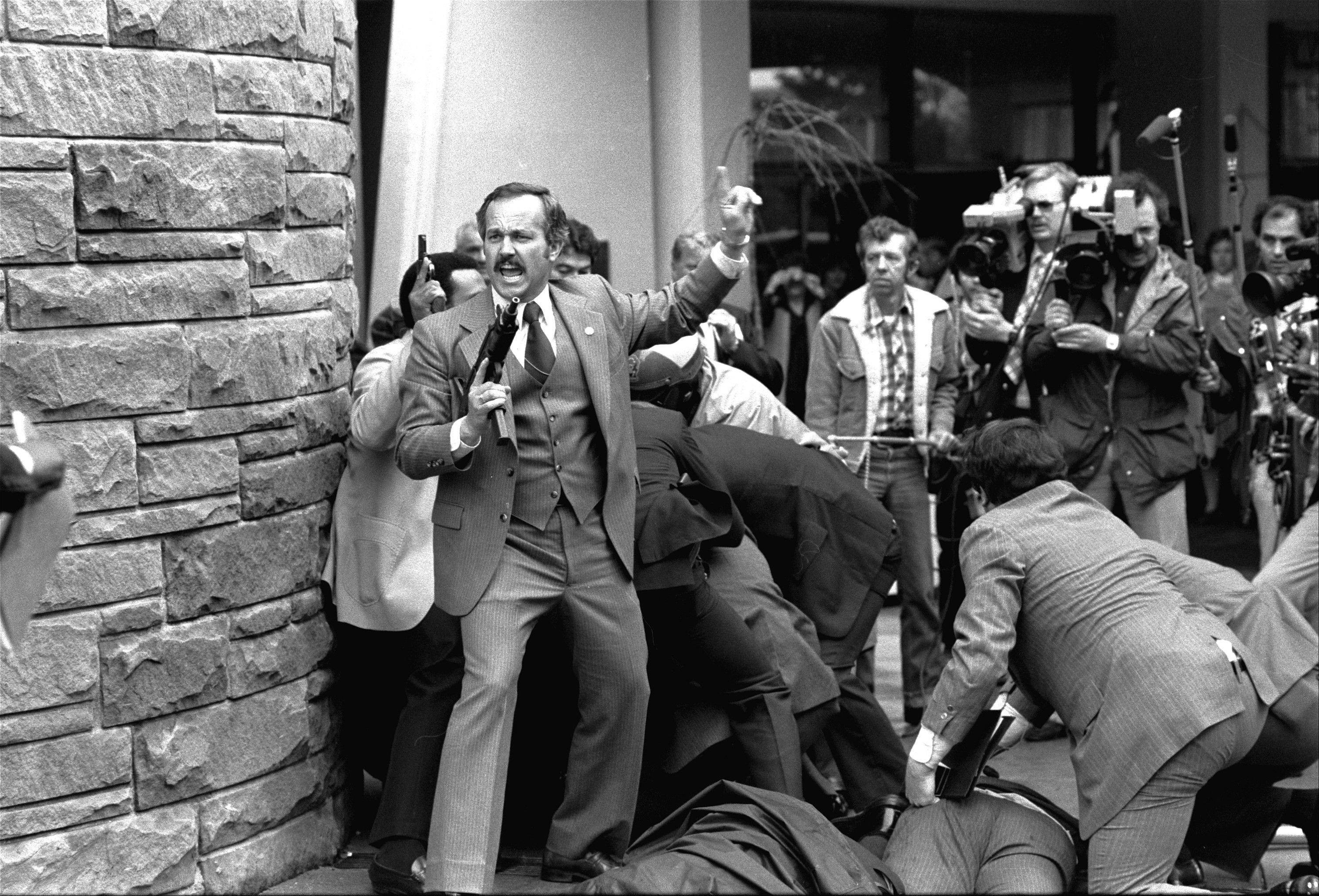 A Secret Service agent, automatic weapon drawn, yells orders after shots were fired at President Ronald Reagan outside a hotel in Washington.