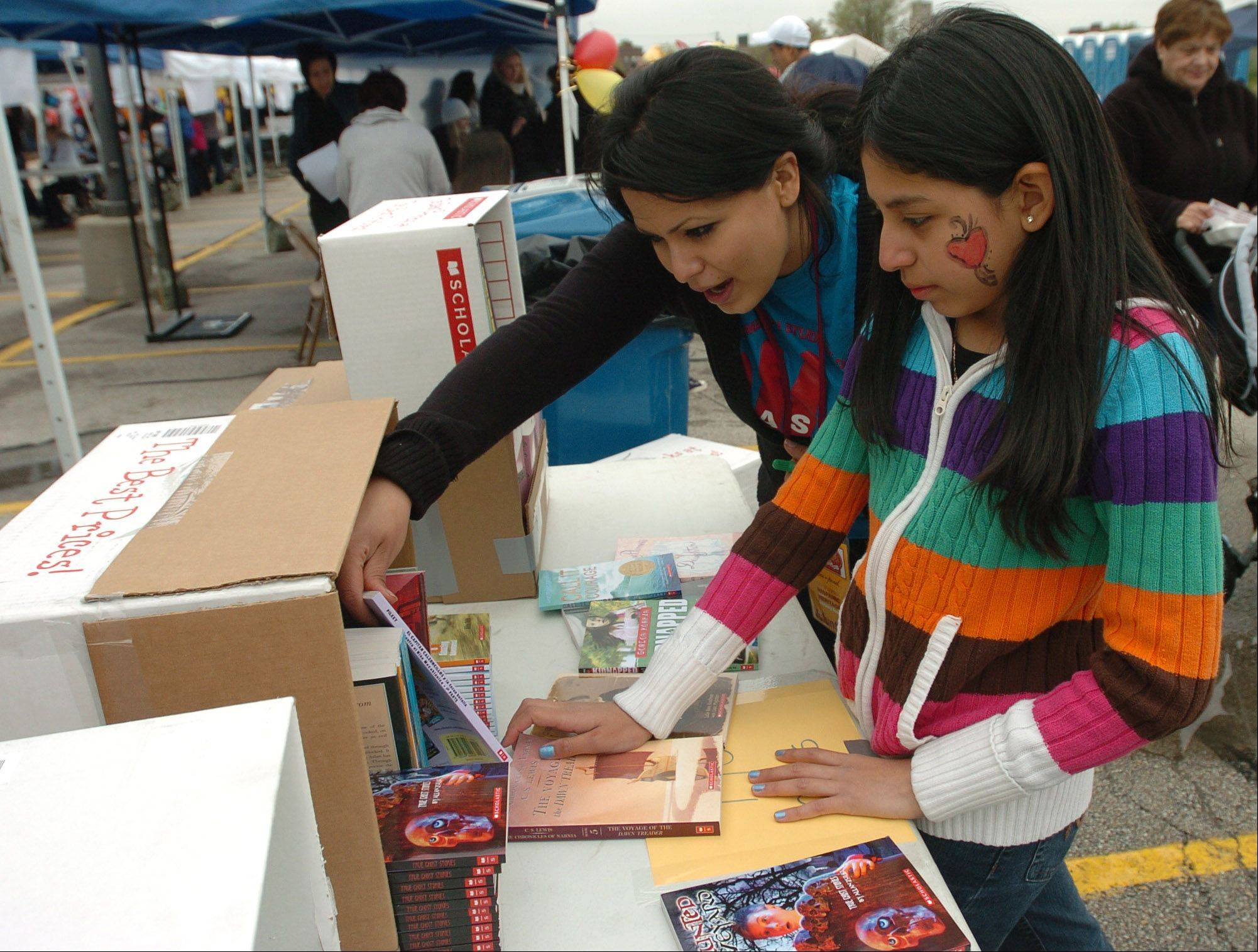 Crystal Sosa of Aurora University helps Lilian Martinez, 11, of Aurora, pick out a free book during the 10th annual El Dia de los Ninos or The Day of the Children literacy festival Saturday in Aurora.