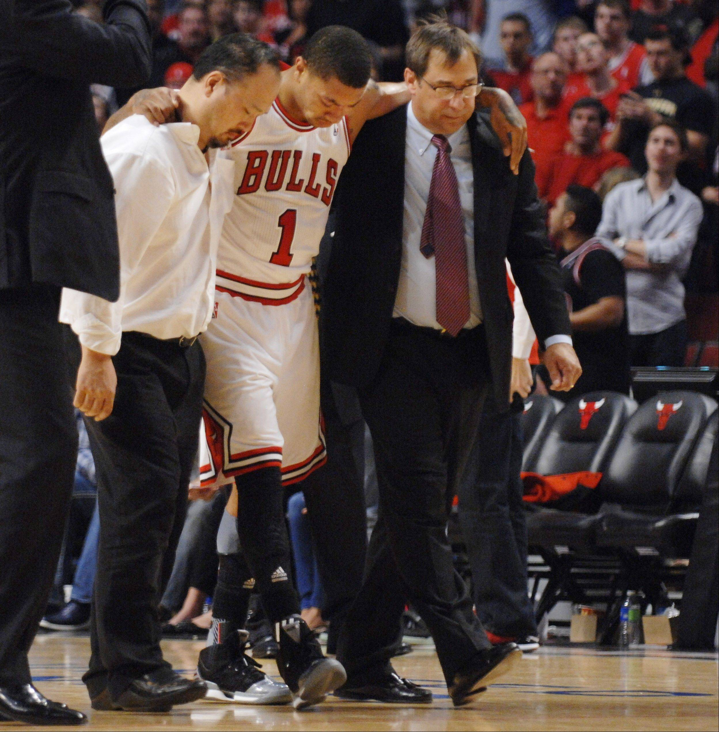 Derrick Rose is assisted off the court after injuring the ACL in his left leg Saturday at the United Center.