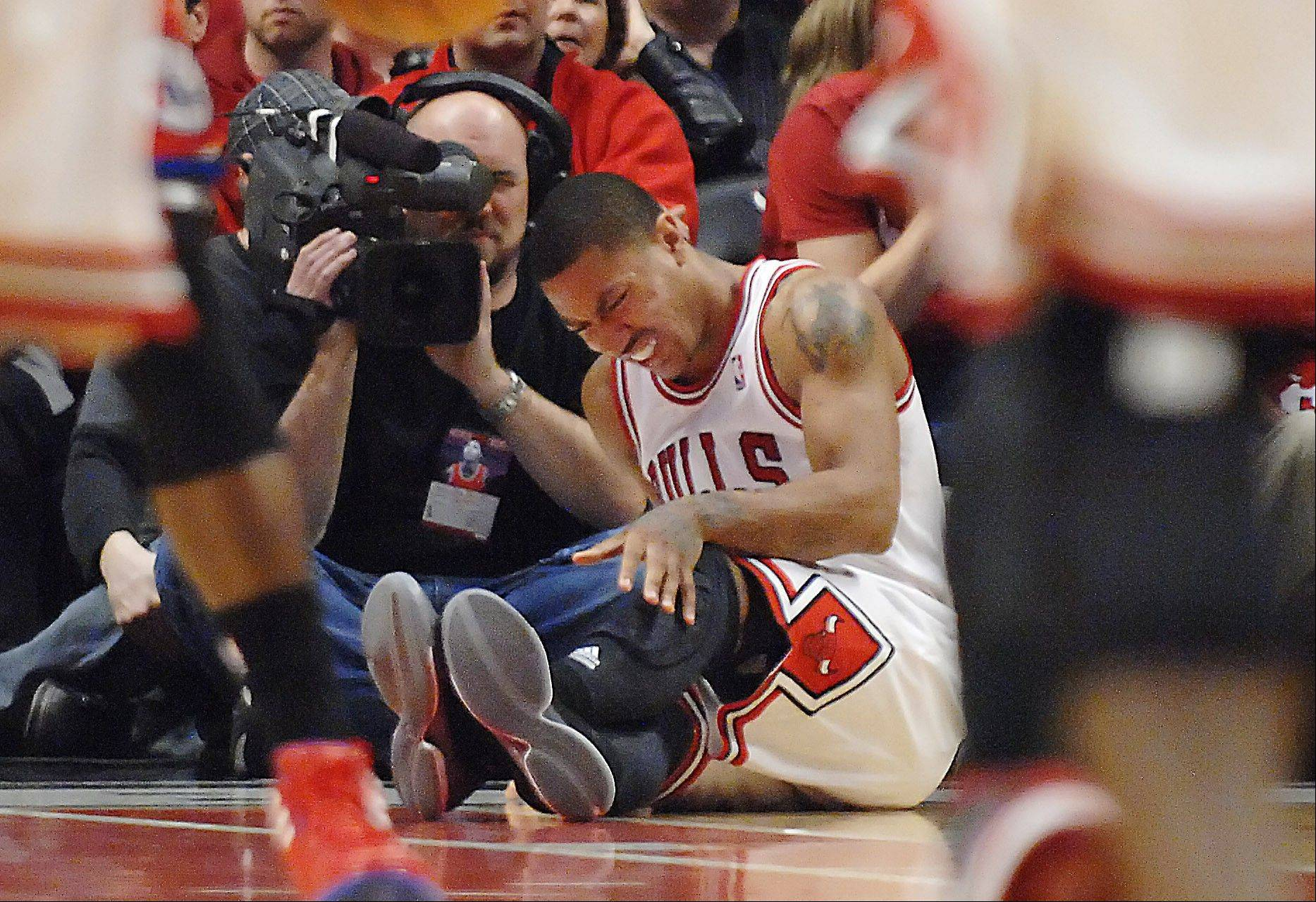 Derrick Rose reats after injuring his leg in the fourth quarter of Game 1 in the first round of the NBA basketball playoffs against the Philadelphia 76ers Saturday, April 28, 2012, in Chicago. The Bulls won 103-91.