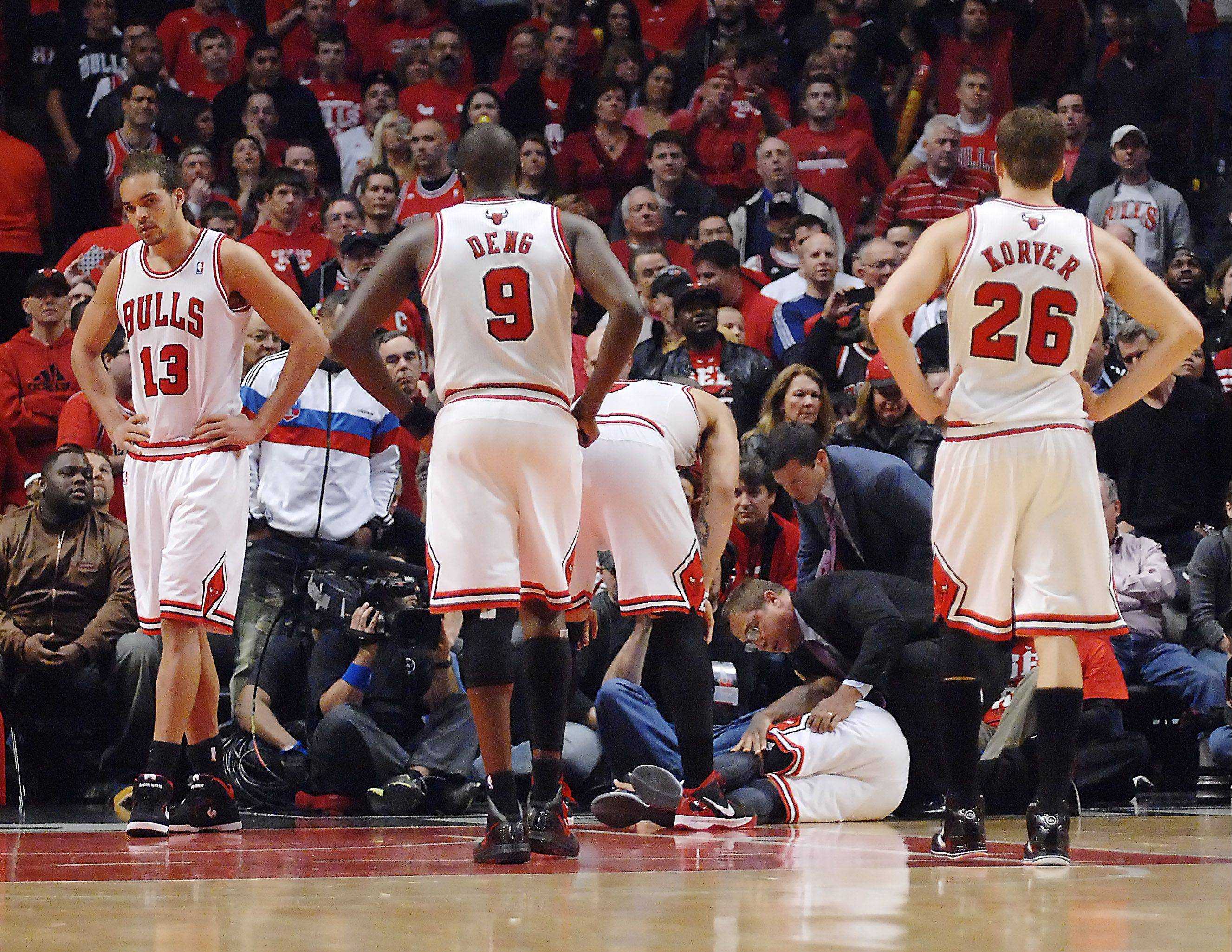 The Bulls react after Derrick Rose injures his knee late in the fourth quarter of their 103-91 win Saturday over the Sixers at the United Center.