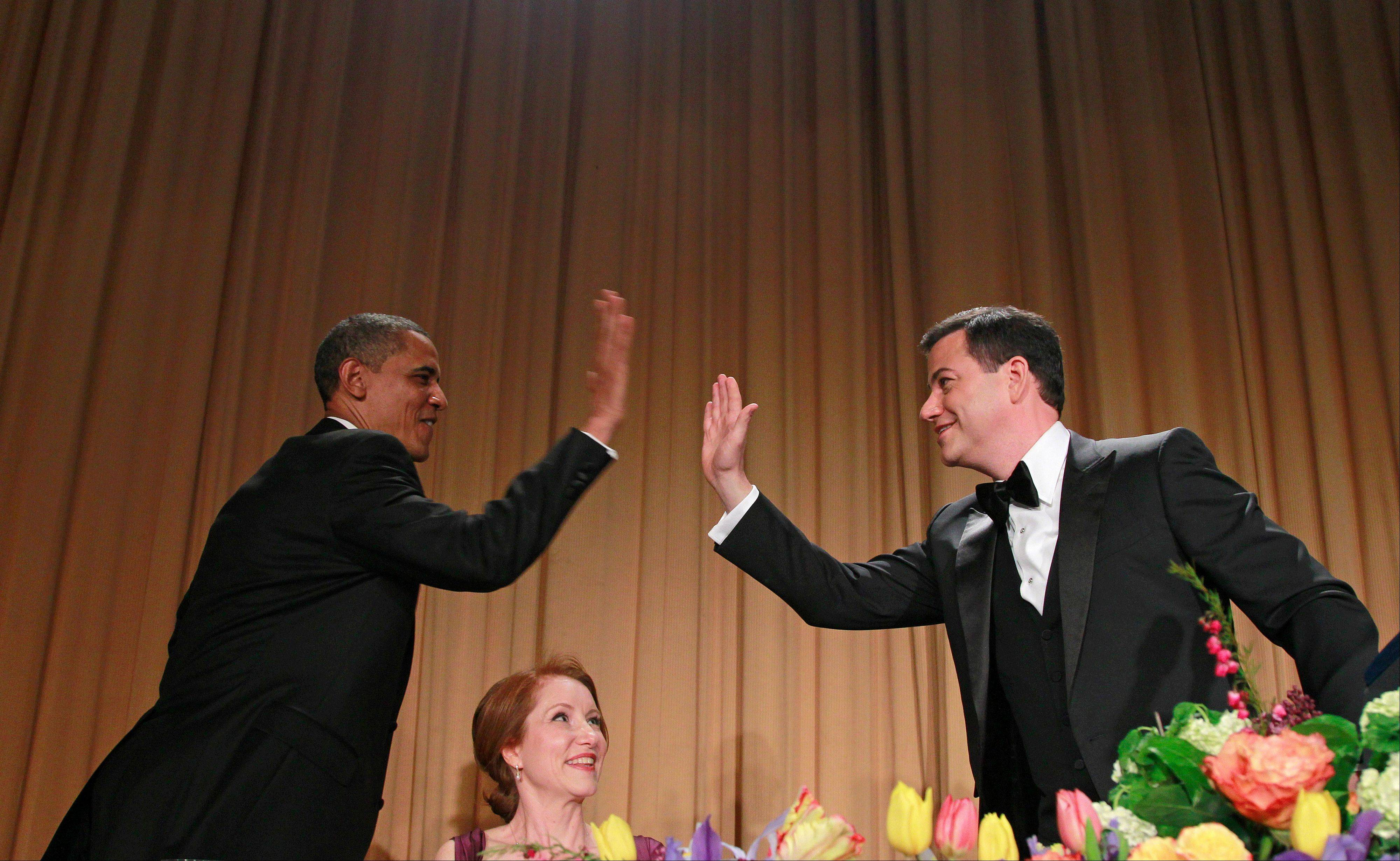 President Barack Obama high-fives late-night comic Jimmy Kimmel as Caren Bohan, a Reuters journalist and president of the White House Correspondents' Association looks on, during the White House Correspondents' Association Dinner on Saturday in Washington.