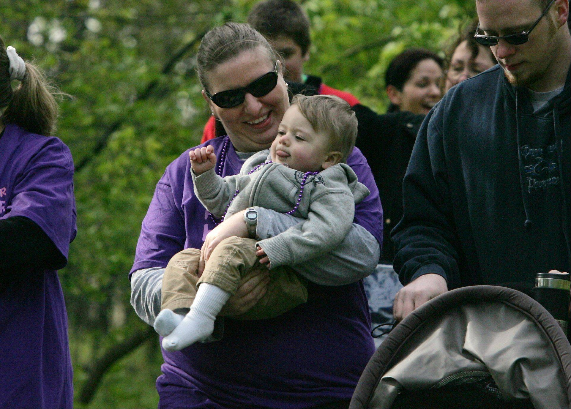 "Cindy Moore, of Schaumburg, holds her one-year-old son, Kyle, as she walks with her husband, Chris, during the March of Dimes' ""March For Babies"" walk Sunday in Busse Woods in Elk Grove Village. The walk raised money to help prevent premature birth, birth defects and infant mortality."