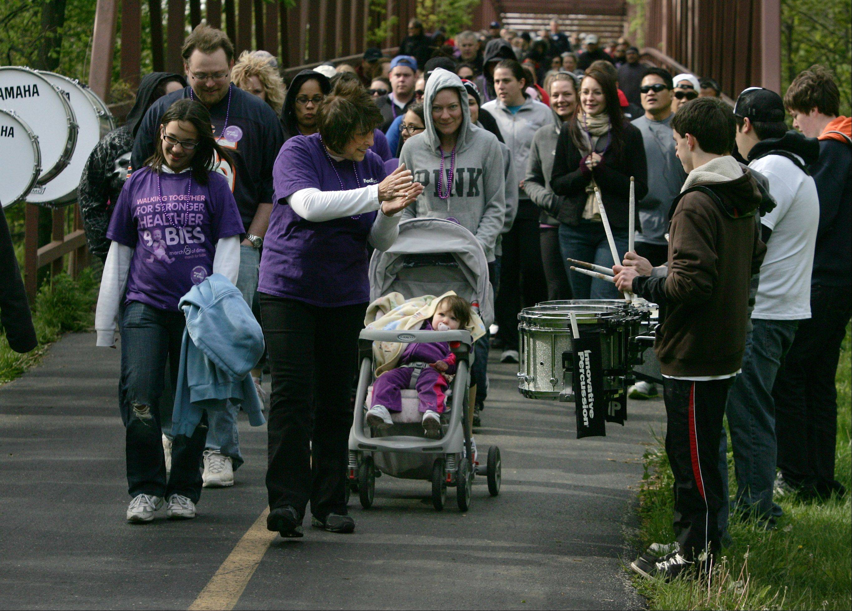 "Lynette Strobel, of Des Plaines, dances as she passes by the drum corps of the Prospect High School marching band Sunday at the start of the March of Dimes' ""March For Babies"" walk in Busse Woods in Elk Grove Village. The walk raised money to help prevent premature birth, birth defects and infant mortality."