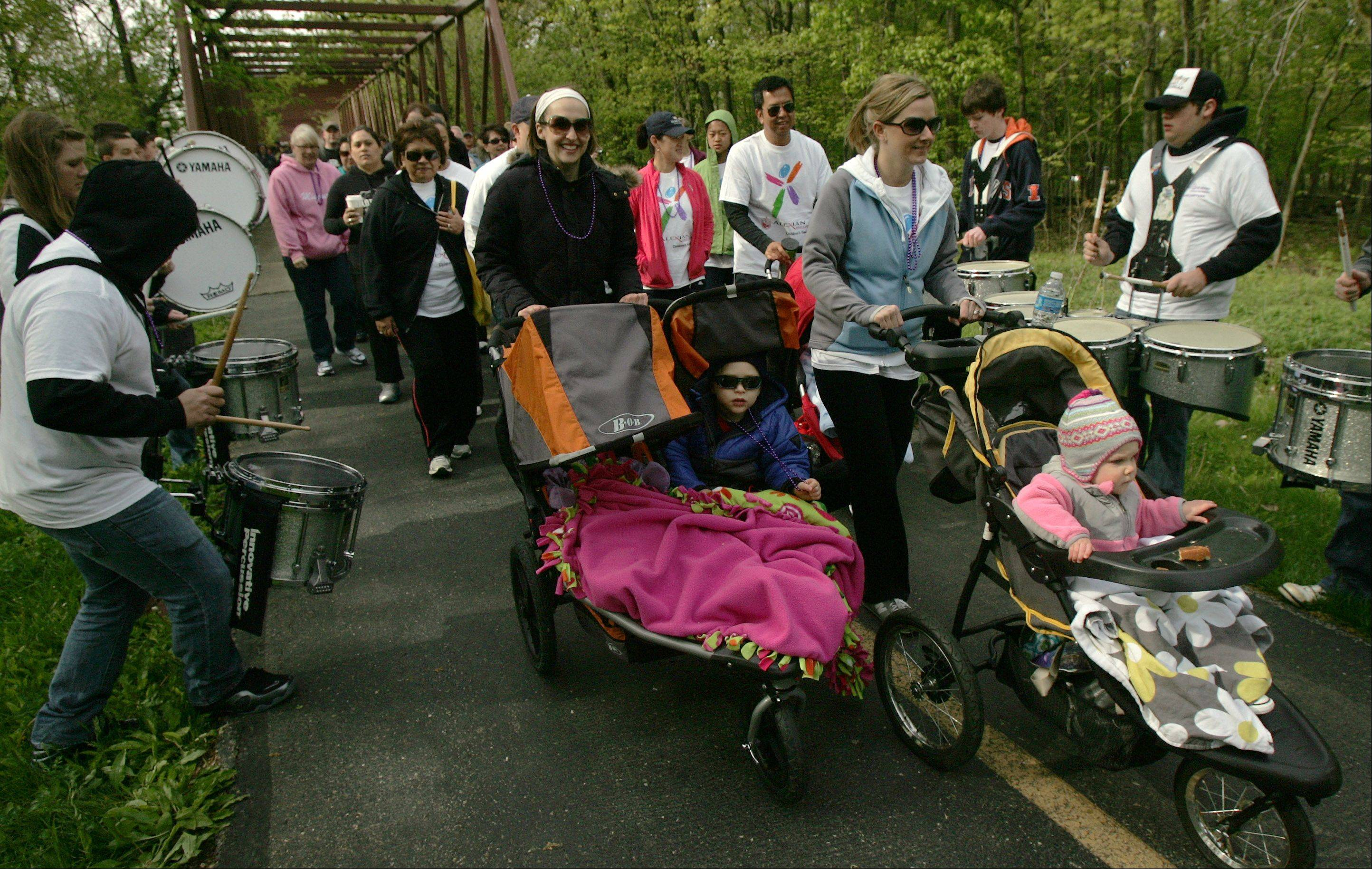 "Walkers pass by the drum corps of the Prospect High School marching band to start the March of Dimes' ""March For Babies"" walk Sunday in Busse Woods in Elk Grove Village."