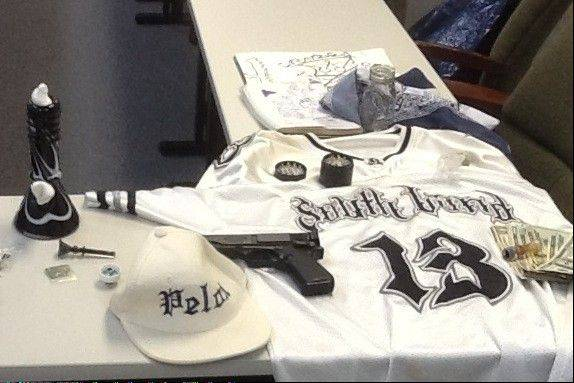 Authorities display a weapon and other items they say were seized in a street gang sweep in Round Lake Park that resulted in a dozen arrests.
