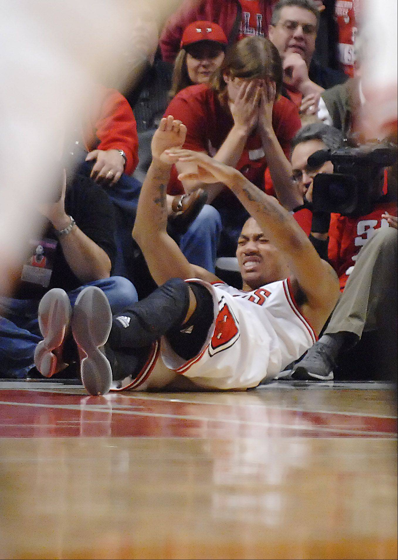A fan reacts as Bulls guard Derrick Rose shows the pain of his left-knee injury late in Saturday's Game 1 victory over the Philadelphia 76ers at the United Center.