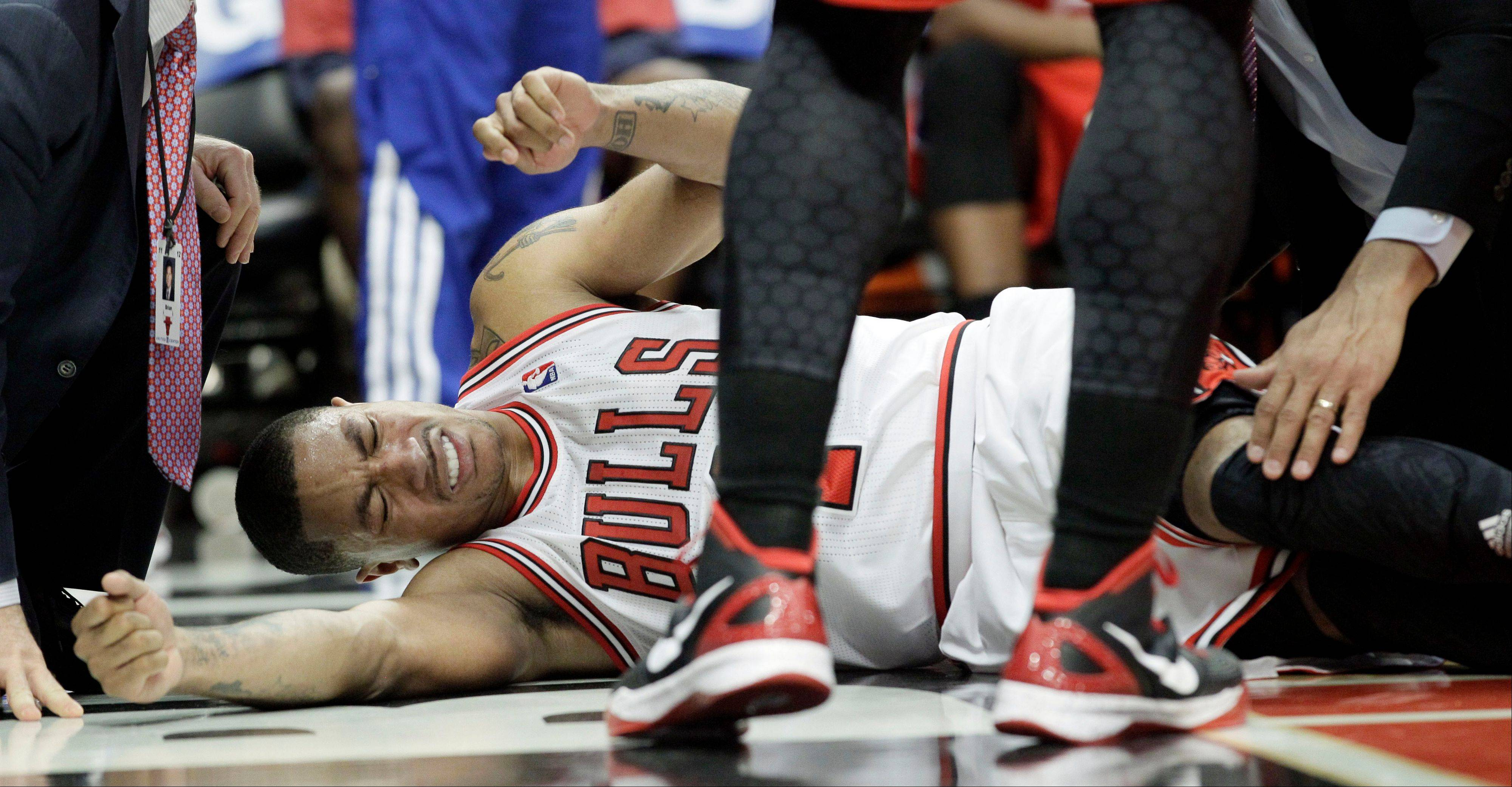 Chicago Bulls guard Derrick Rose reacts after an injury Saturday during the fourth quarter of Game 1 in the first round of the NBA basketball playoffs against the Philadelphia 76ers in Chicago. The Bulls won 103-91.