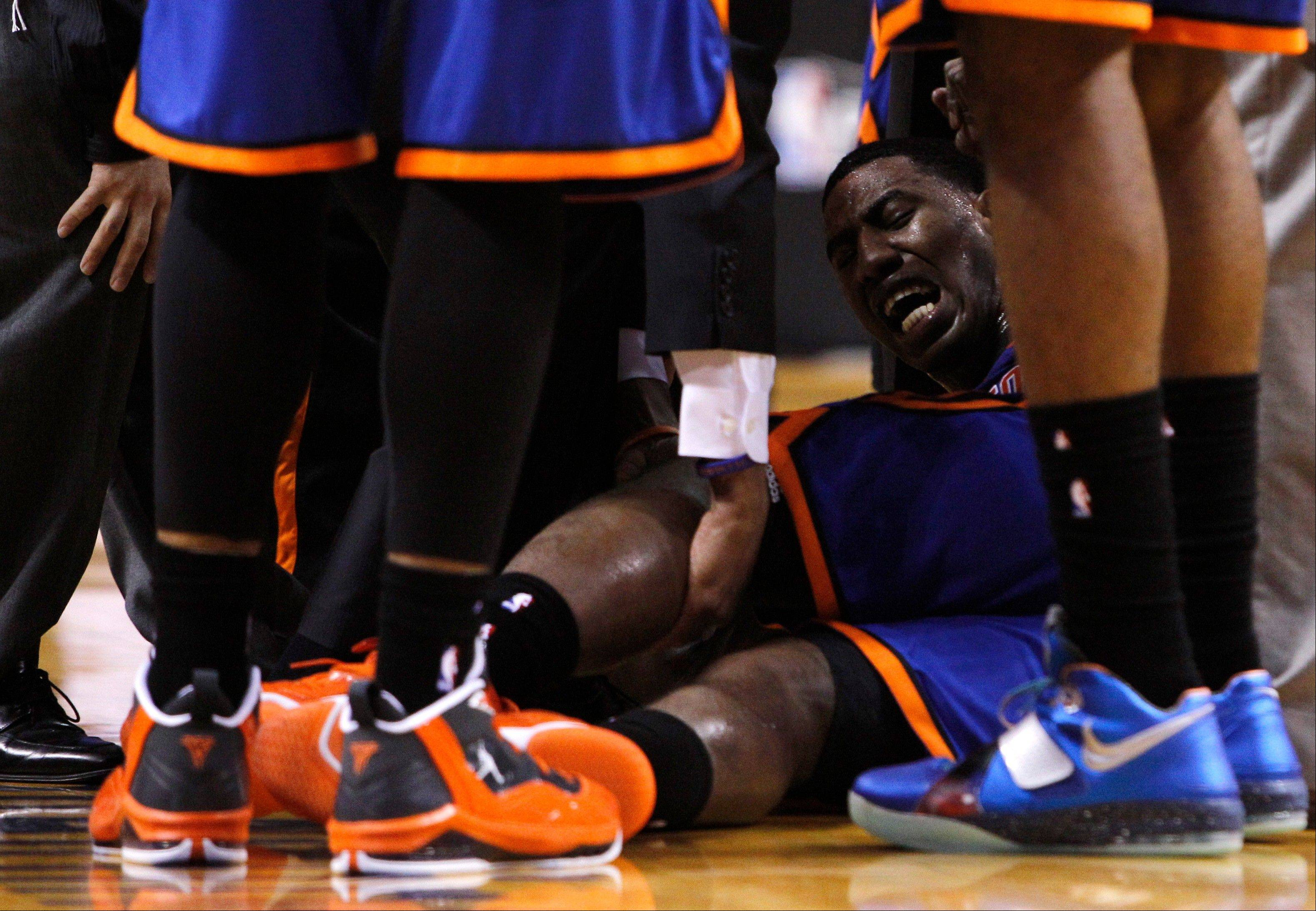 New York Knicks' Iman Shumpert, center, is helped up from the court after an injury Saturday in the second half during an NBA basketball game against the Miami Heat in the first round of the Eastern Conference playoffs in Miami.