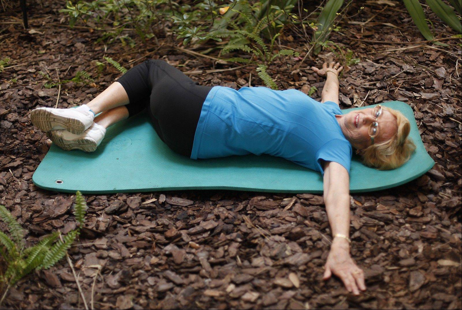 JoAnn French, 72, demonstrates a knee-drops pose.