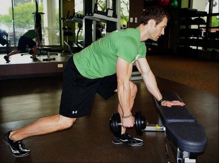 To start the staggered one arm row: Take a staggered position with one foot forward and your same hand braced on a bench. Take hold of a dumbbell with your right hand.