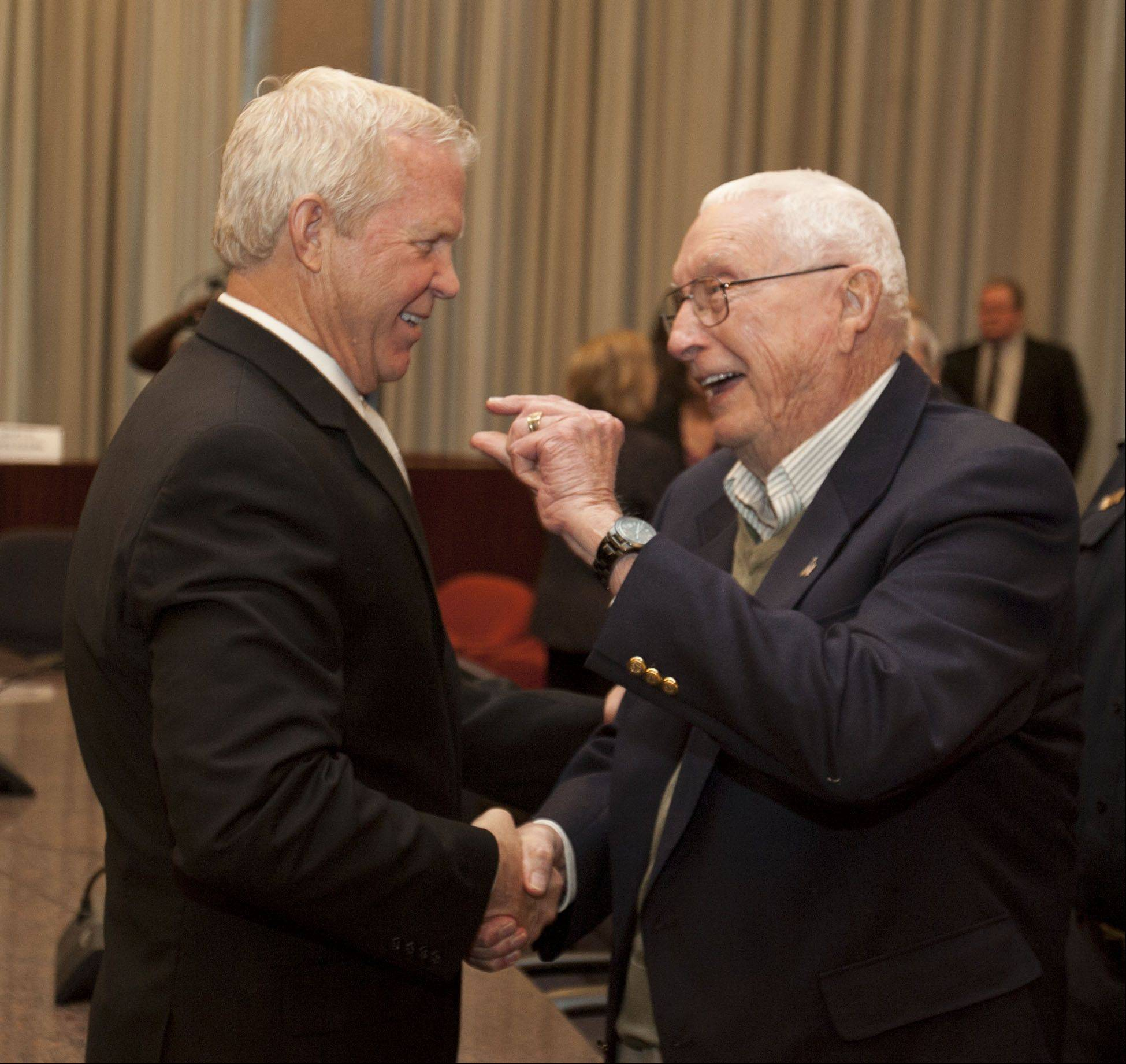 Jack McCambridge, former chairman of the Naperville Board of Fire and Police Commissions, congratulates the city's next police chief, Bob Marshall, during a ceremony Tuesday.