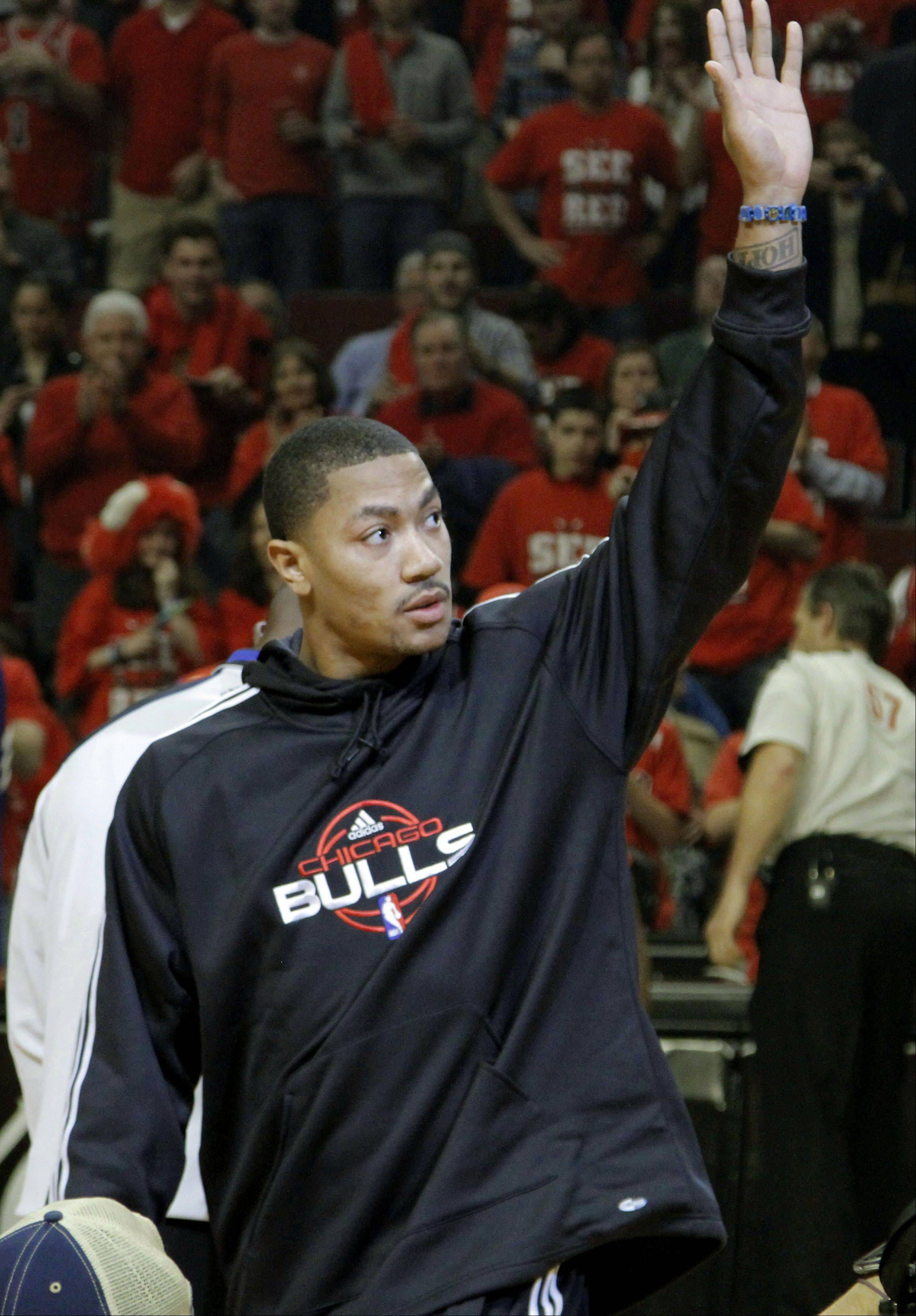 Chicago Bulls' Derrick Rose waves to the crowd after bringing out the game ball.