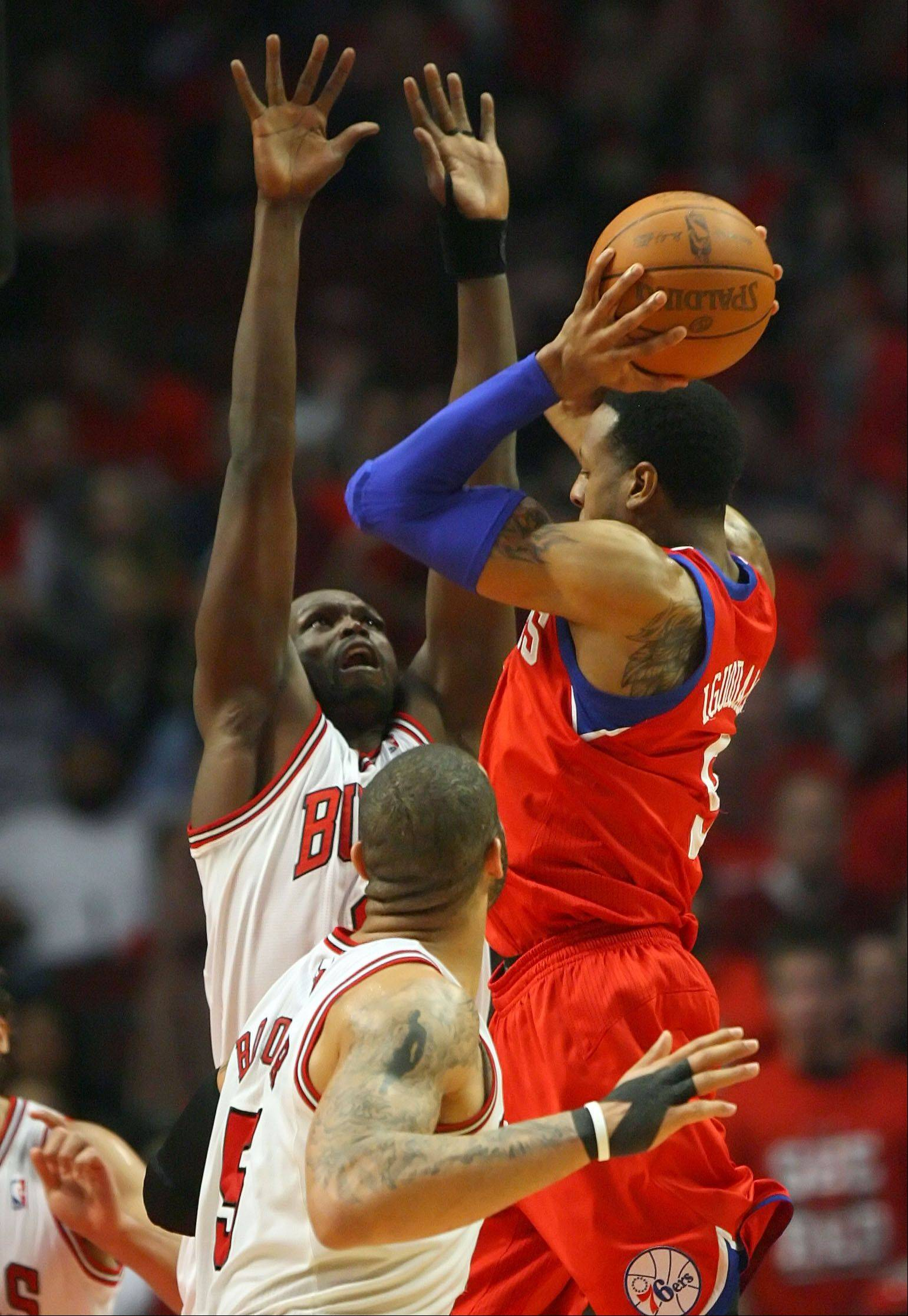 Chicago Bulls' Luol Deng and Philadelphia 76ers' Andre Iguodala battle for a rebound.