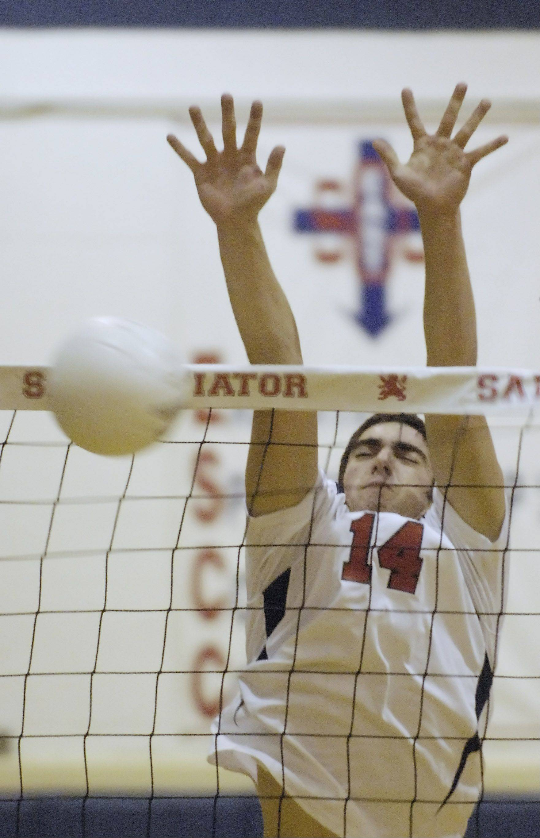 St. Viator's Nick Frank blocks a ball at the net against Marist.