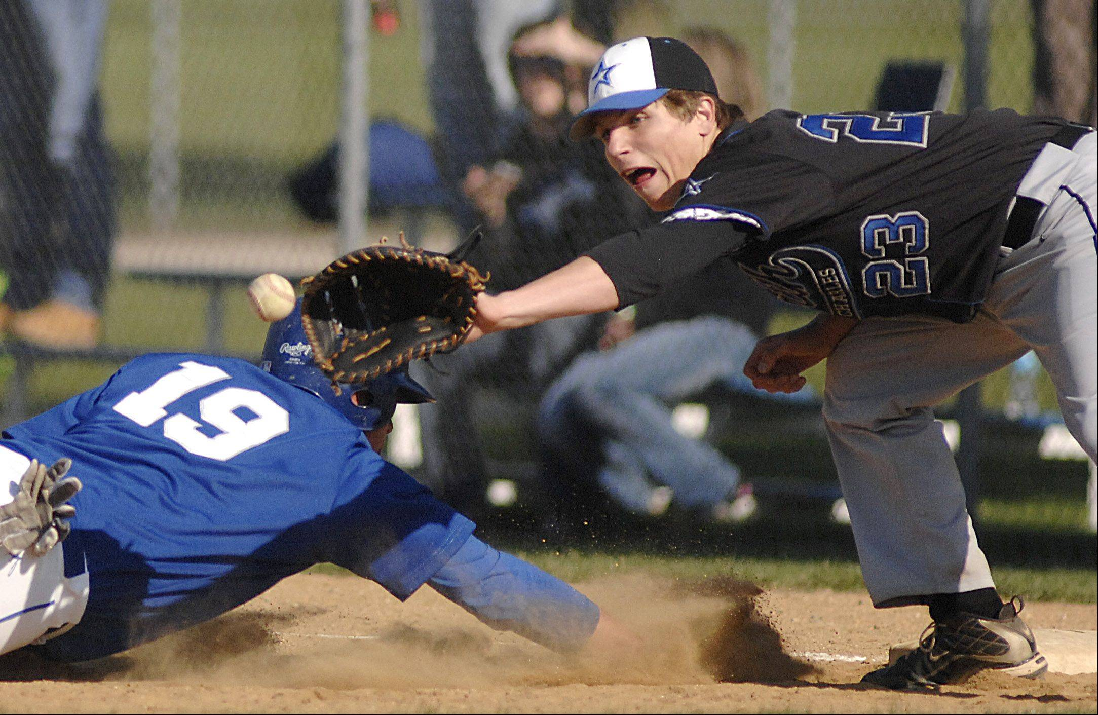 Geneva's Anthony Bragg is safe back on first base St. Charles North's Ryan Thomas eyes the ball Thursday.