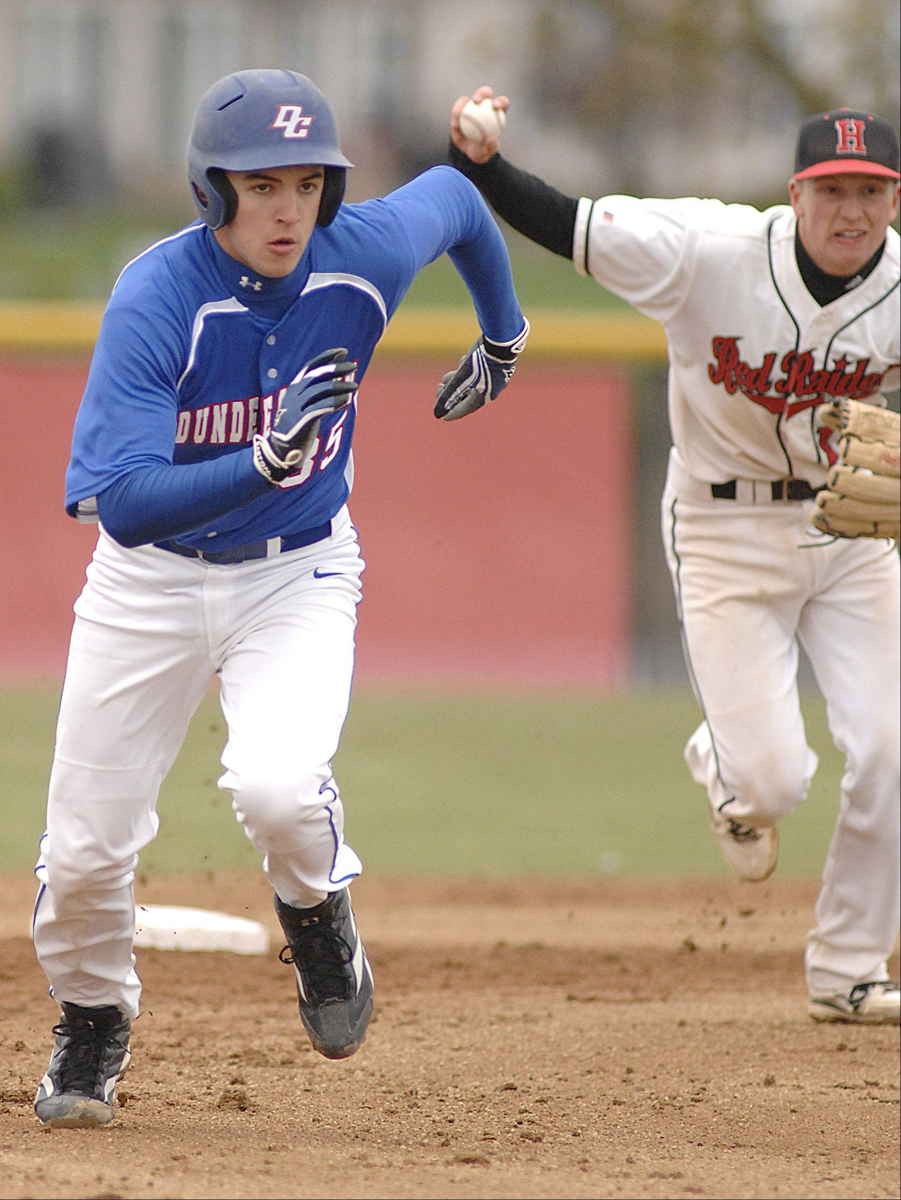 Dundee-Crown's Kyle Bernhard is chased down by Huntley's Jordan Chuipek as he heads for third base Saturday.