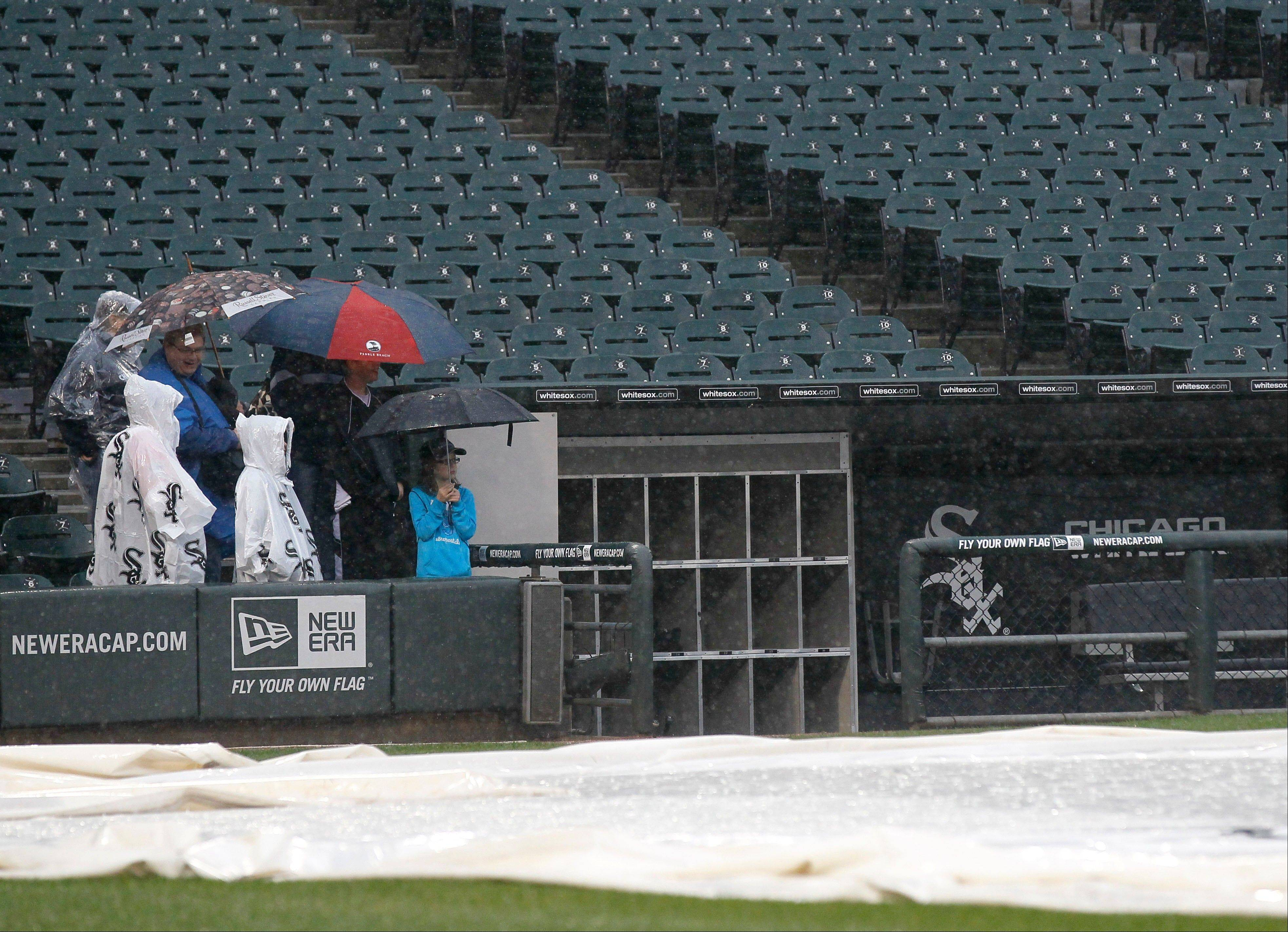 White Sox fans wait in a steady rainfall at the Sox dugout before the game between the Sox and the Cleveland Indians.