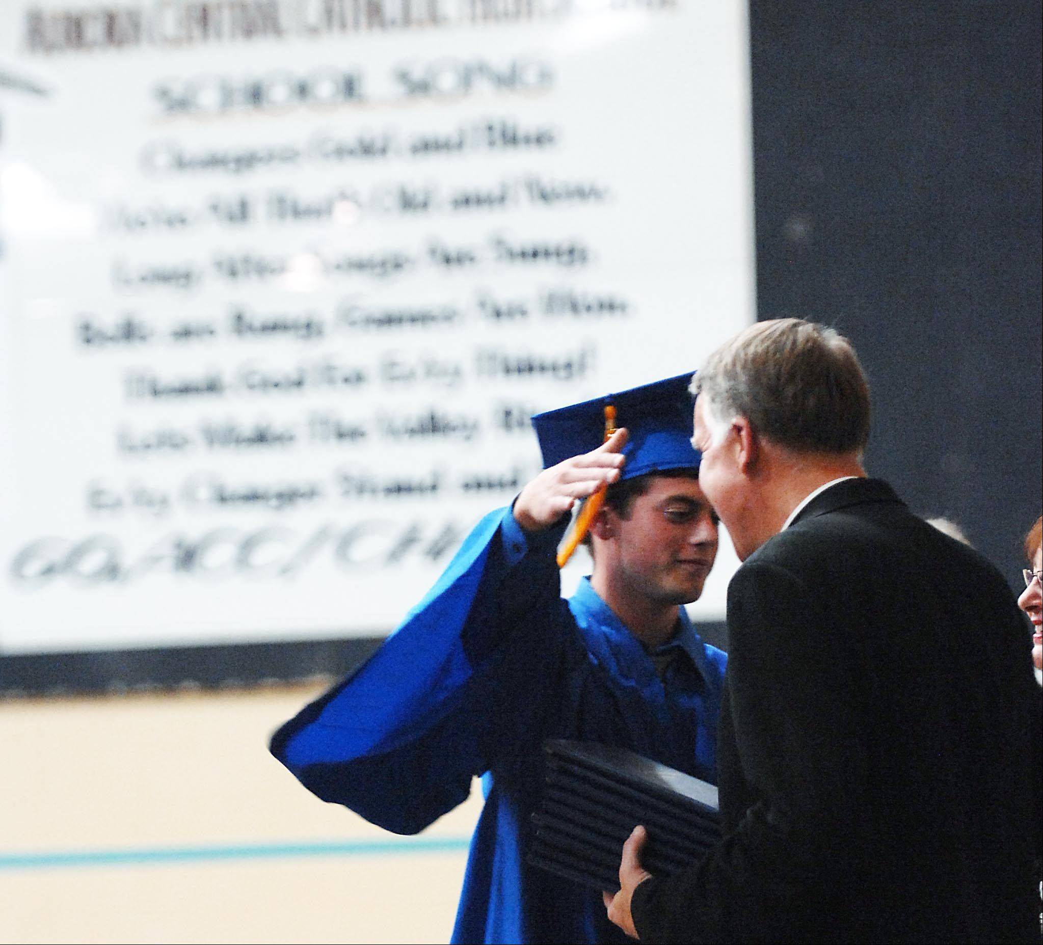 Aaron Blatner hugs the Rev. F. William Etheredge, Principal of Aurora Central Catholic High School at Thursday's graduation .
