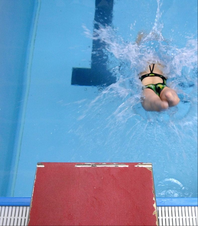 Swimmer Amy Chapman of Batavia dives into the pool at swim practice in Aurora.