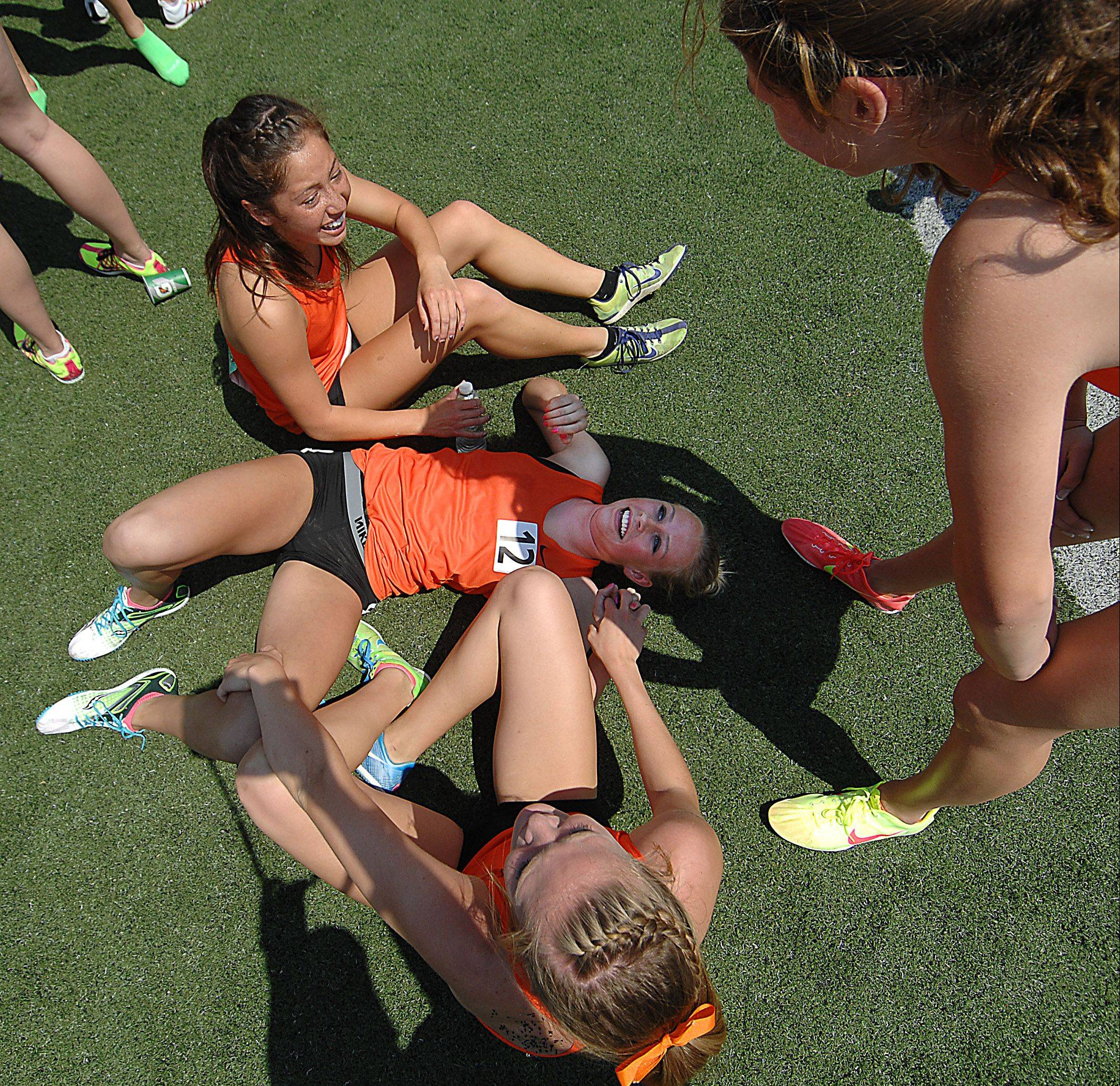Wheaton Warrenville South's McKenna Kiple lies on the ground as teammates Amy Yong, top, Hope Schmelzle, bottom, and Erin Hermann laugh with her after they set a meet record in the 3,200-meter relay Saturday in Charleston.