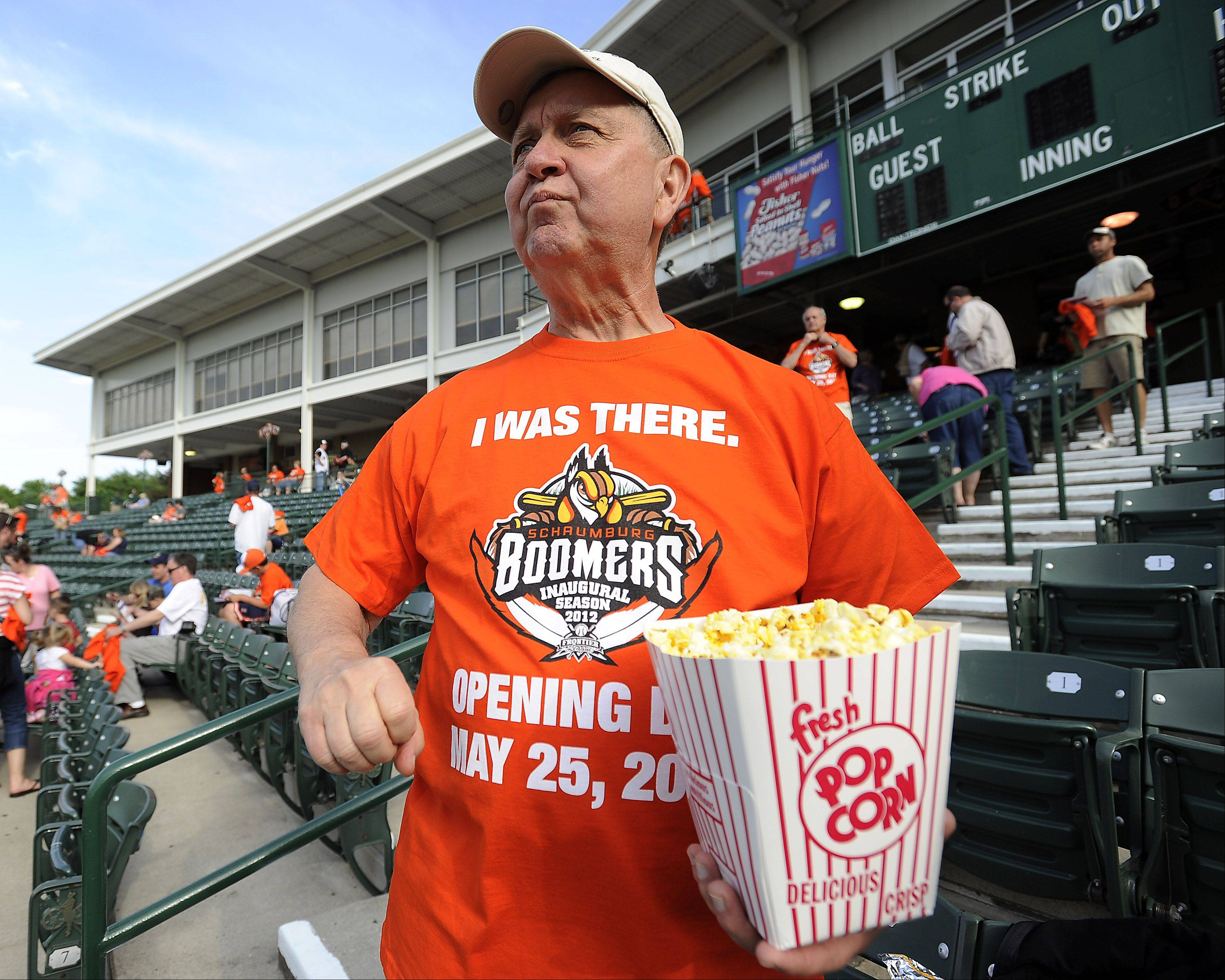 Boomers fan Len Pergander of Mundelein enjoys the action on the field with his popcorn on opening night for the Schaumburg Boomers .