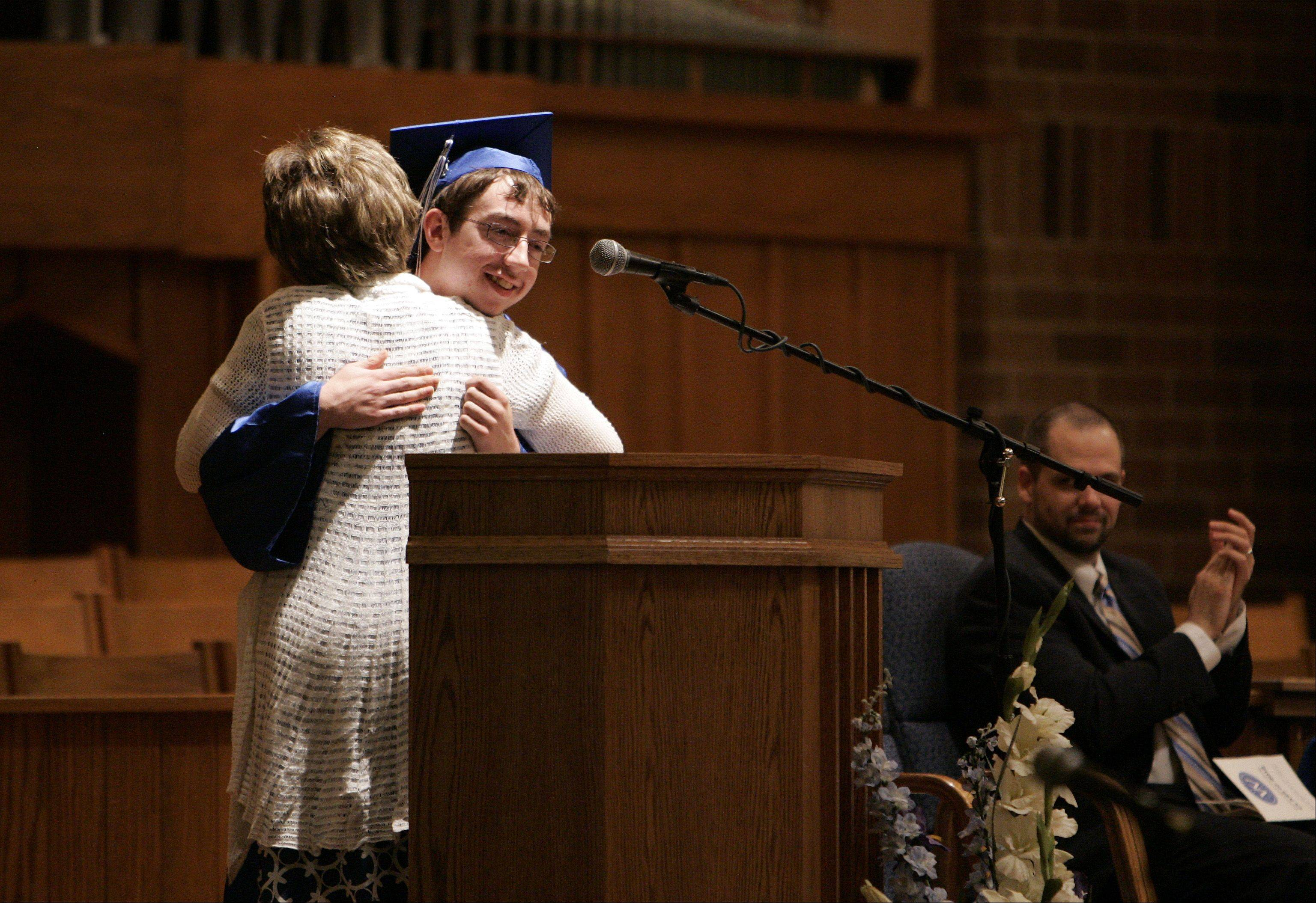 Valedictorian and student government president Kyle Christensen receives a hug from principal Carolyn Palmer during the Westminster Christian High School graduation ceremony.