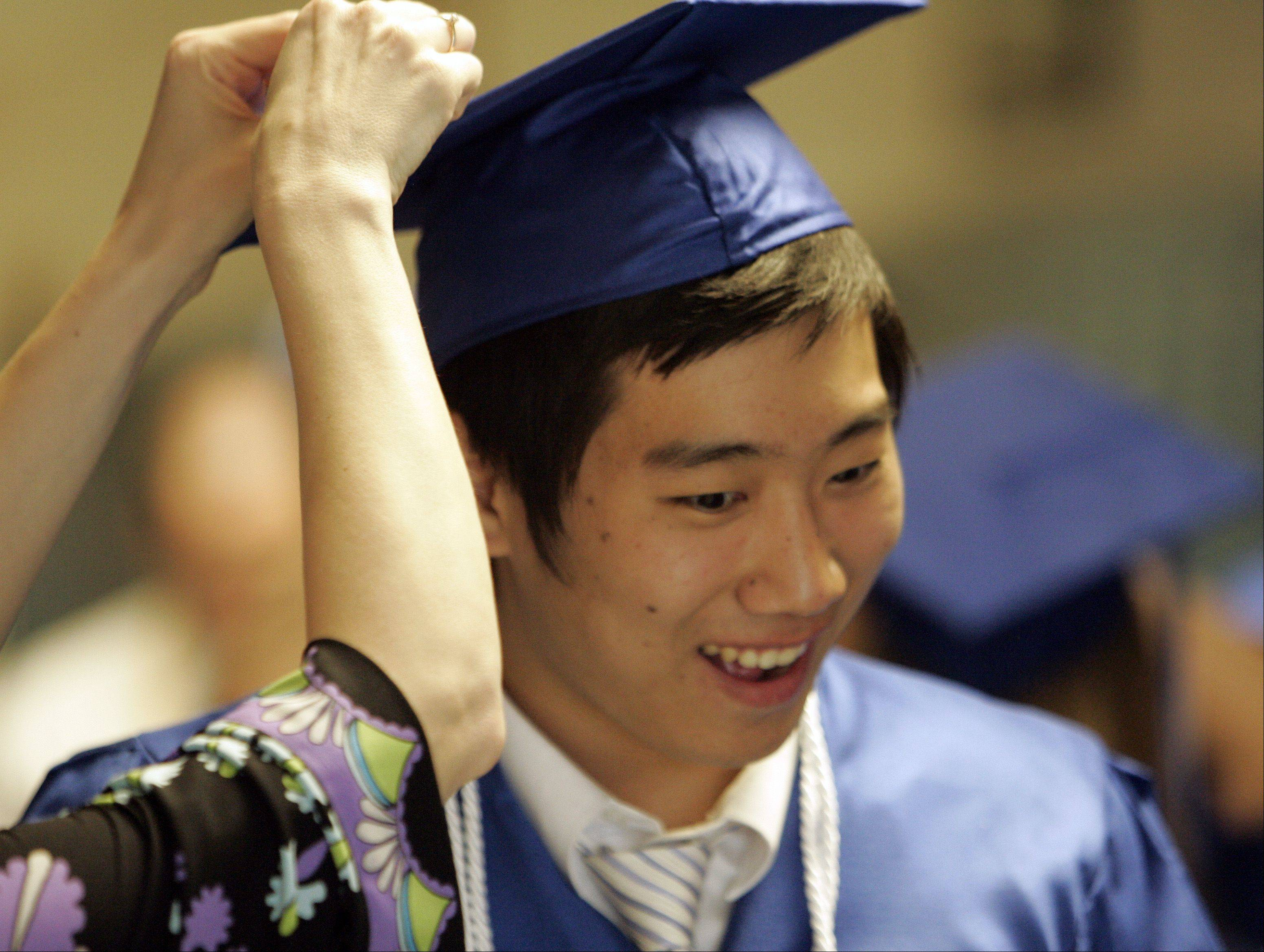 Sion Lee gets some help with his mortar board before the Westminster Christian High School graduation ceremony.