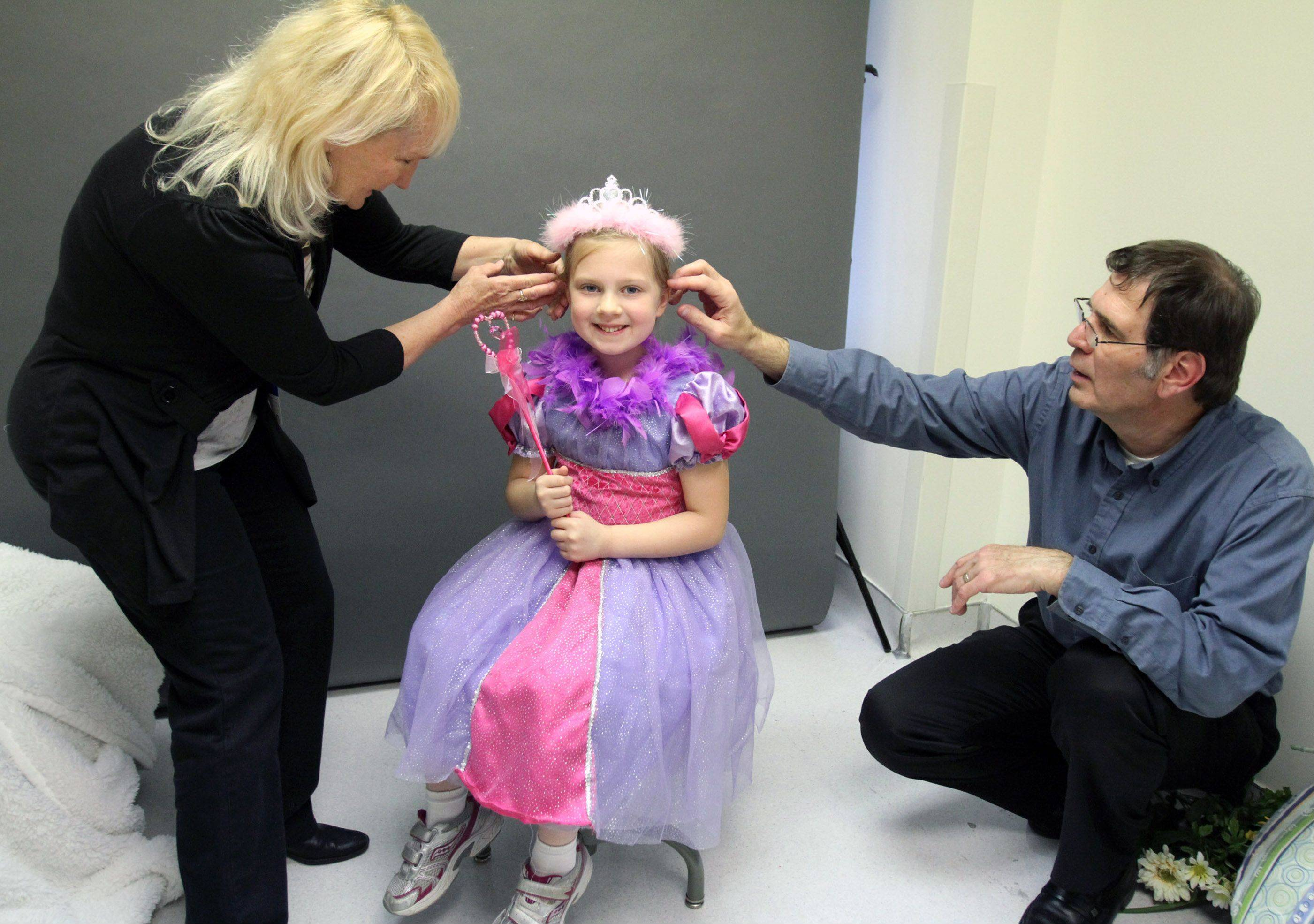 Sharon and Ray adjust 6-year-old Brooke Ames's hair before daughter Jennifer takes a portrait at Children's Memorial Hospital. Brooke's brother Drew, 4, is receiving treatment at the hospital. The Weigands offer to take portraits of siblings and parents of children facing cancer. The Ames family is from Wheaton.