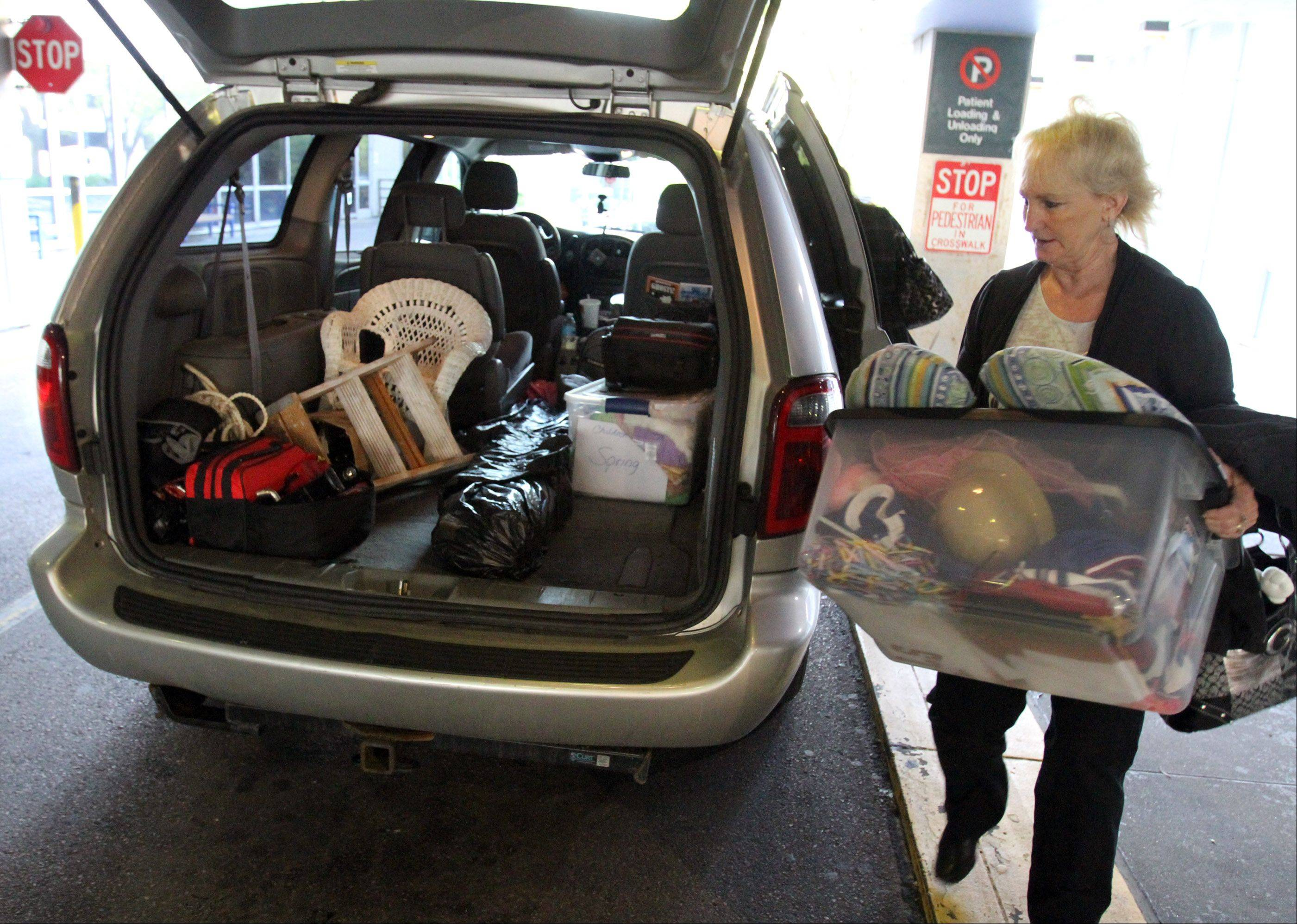 Sharon Weigand unloads a carton of costumes and hats for a photo session at Children's Memorial Hospital.