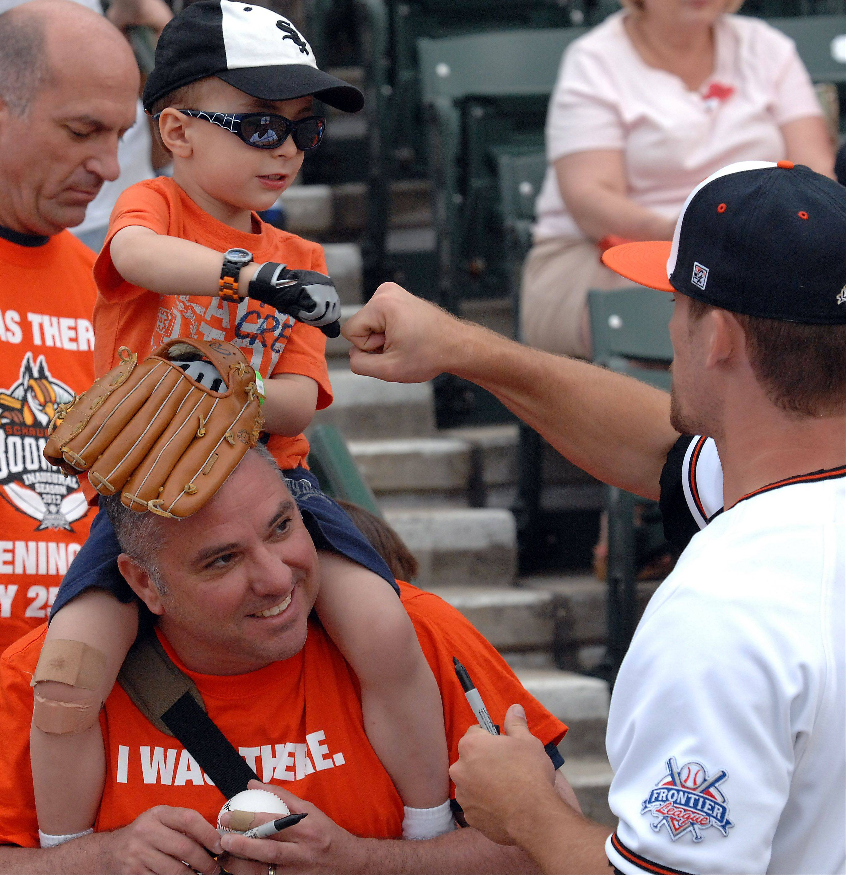 Baseball fans Brian Dykes and his son Calvin,3, of Glen Ellyn bump fists with player Chad Mozingo at Boomers Stadium in Schaumburg on Friday.