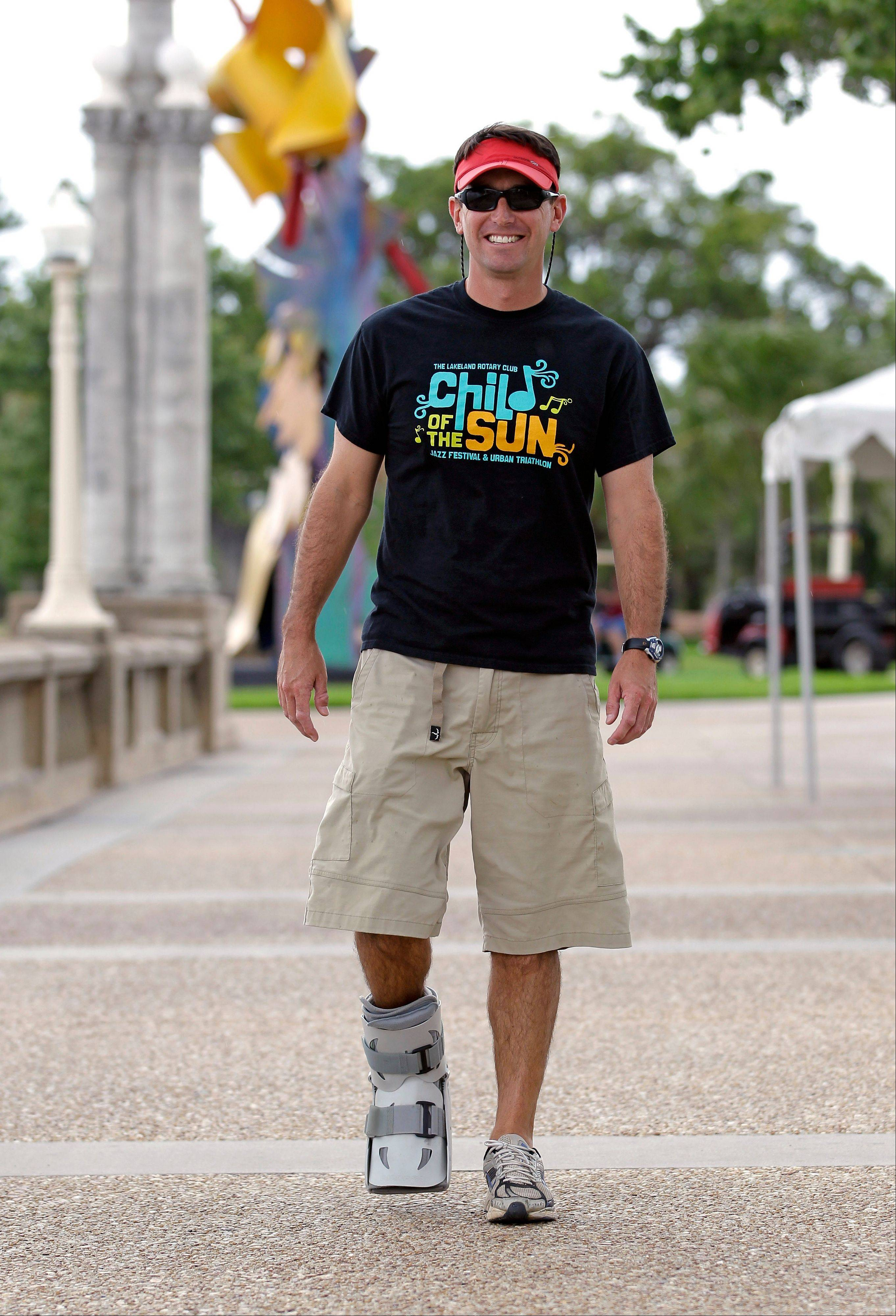Greg Farris walks while wearing a protective boot as he helps set up for a weekend triathlon event in Lakeland, Fla. Farris injured his foot while running in barefoot running shoes.